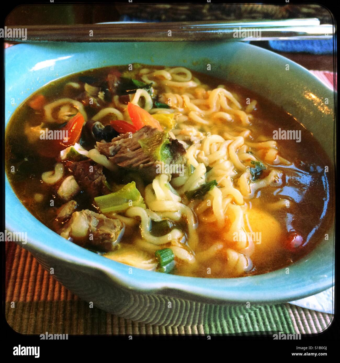 A bowl of homemade spicy beef ramen soup. - Stock Image