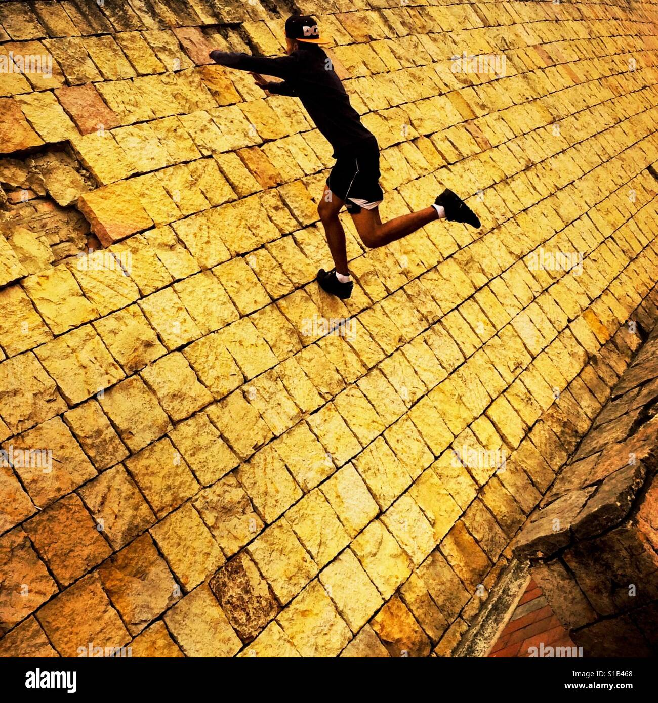 A Colombian parkour runner jumps on the wall during a free running training session held in a park in Kennedy, Bogotá, - Stock Image