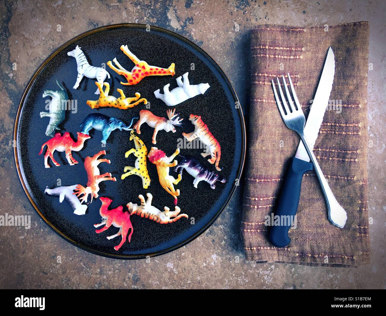 Plastic toy animals on a plate next to a knife and fork. - Stock Image