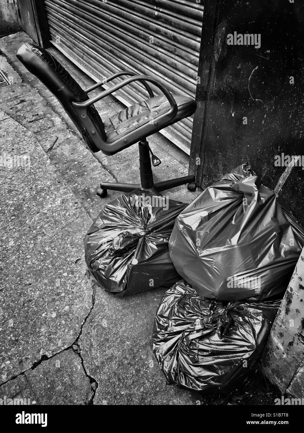 An office chair abandoned next to some rubbish sacks on a city street in the UK - Stock Image