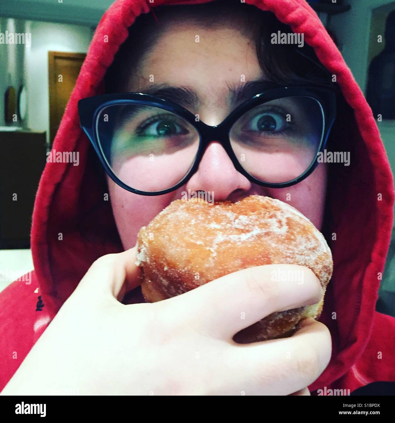 Girl with big glasses red hoodie and pink cheeks biting into a big jam doughnut - Stock Image