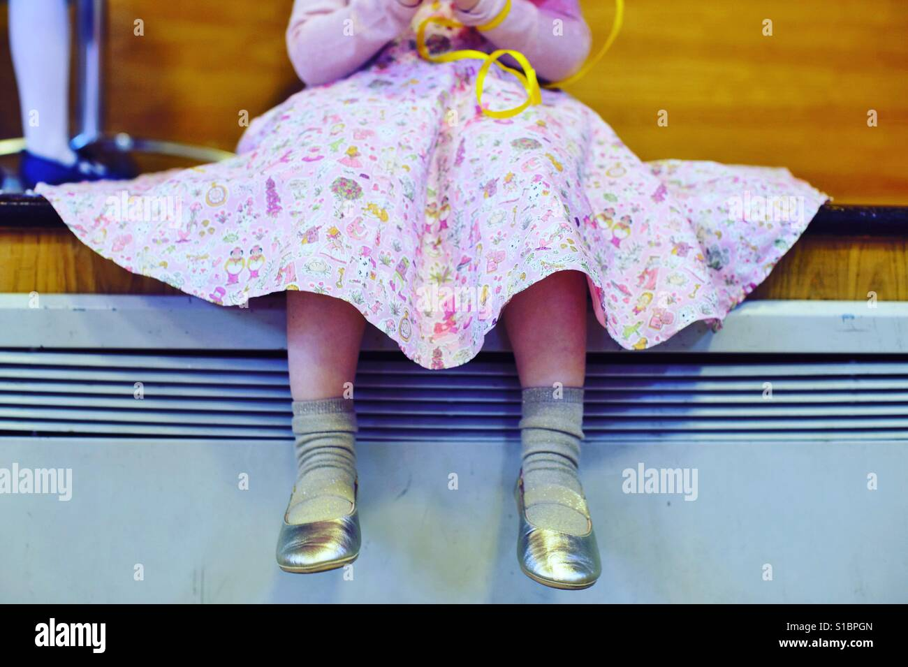 Little girl sitting with good shoes and pink full skirt - Stock Image