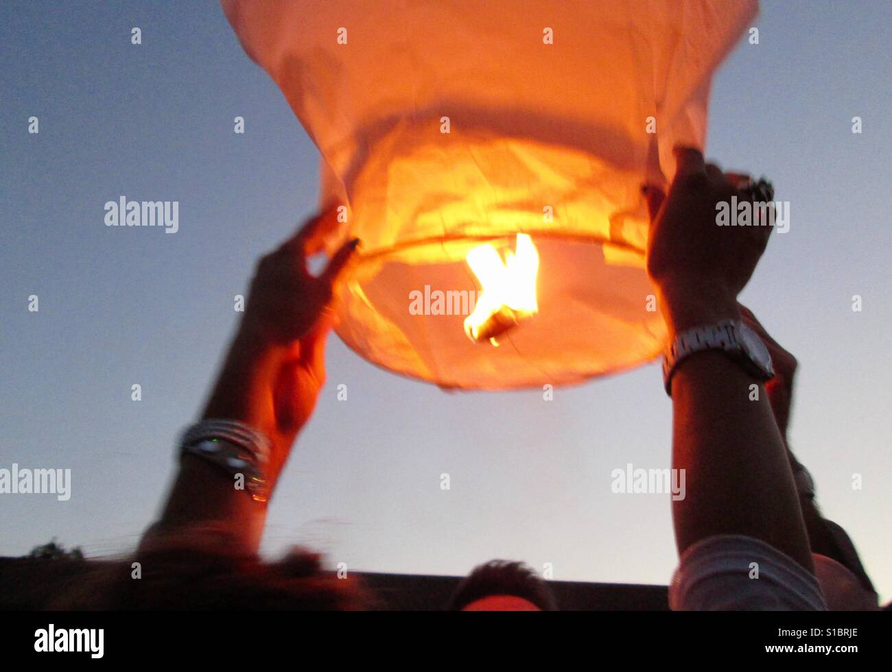 launch of the Chinese lantern at a wedding human hand real people Flame holding sky one person lifestyles Burning - Stock Image
