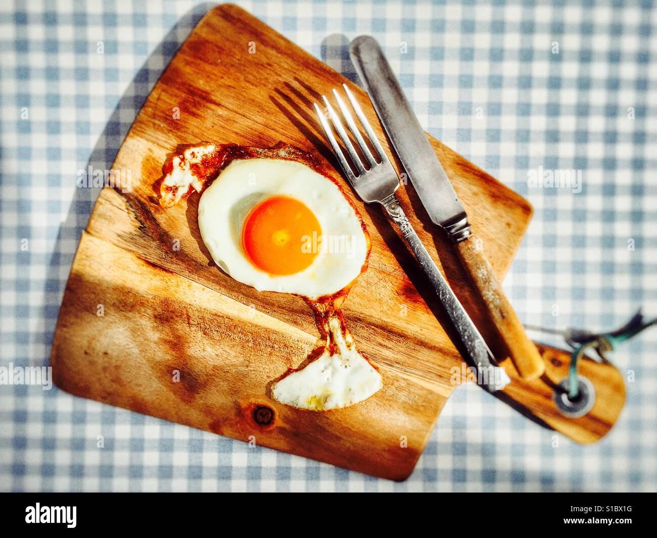 Fried egg on wooden serving board - Stock Image