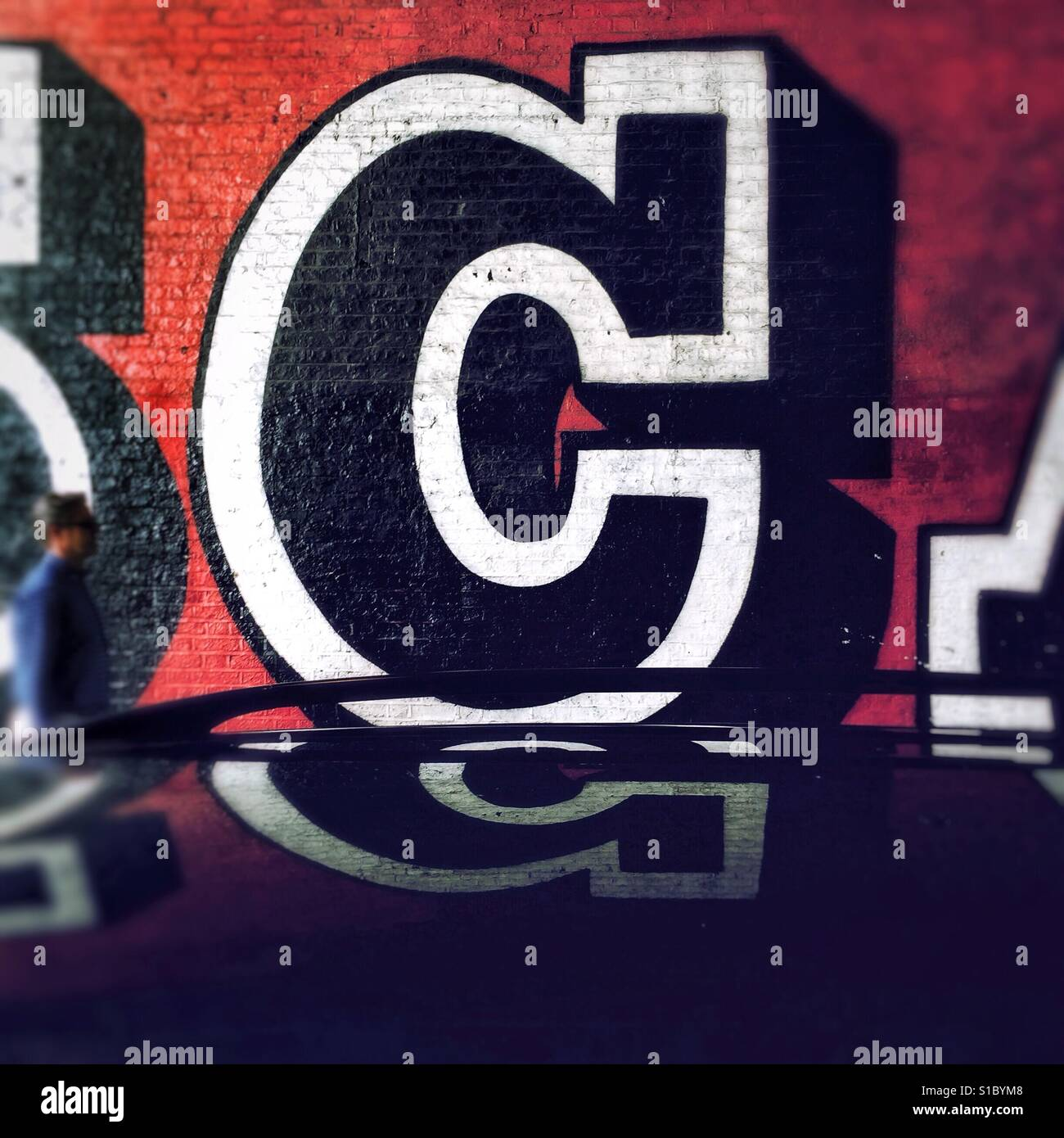 Detail from graffiti art by street artist Ben Eine, showing a colourful, stylised letter C, reflected on a car roof - Stock Image