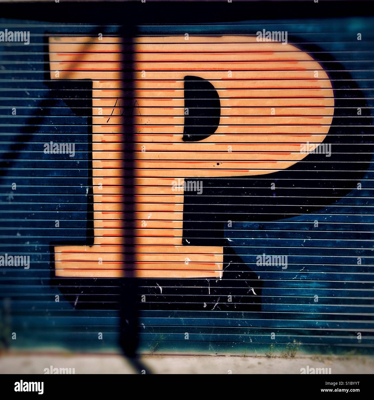 Detail from graffiti art by street artist Ben Eine, showing a colourful, stylised letter P painted onto shutters. - Stock Image