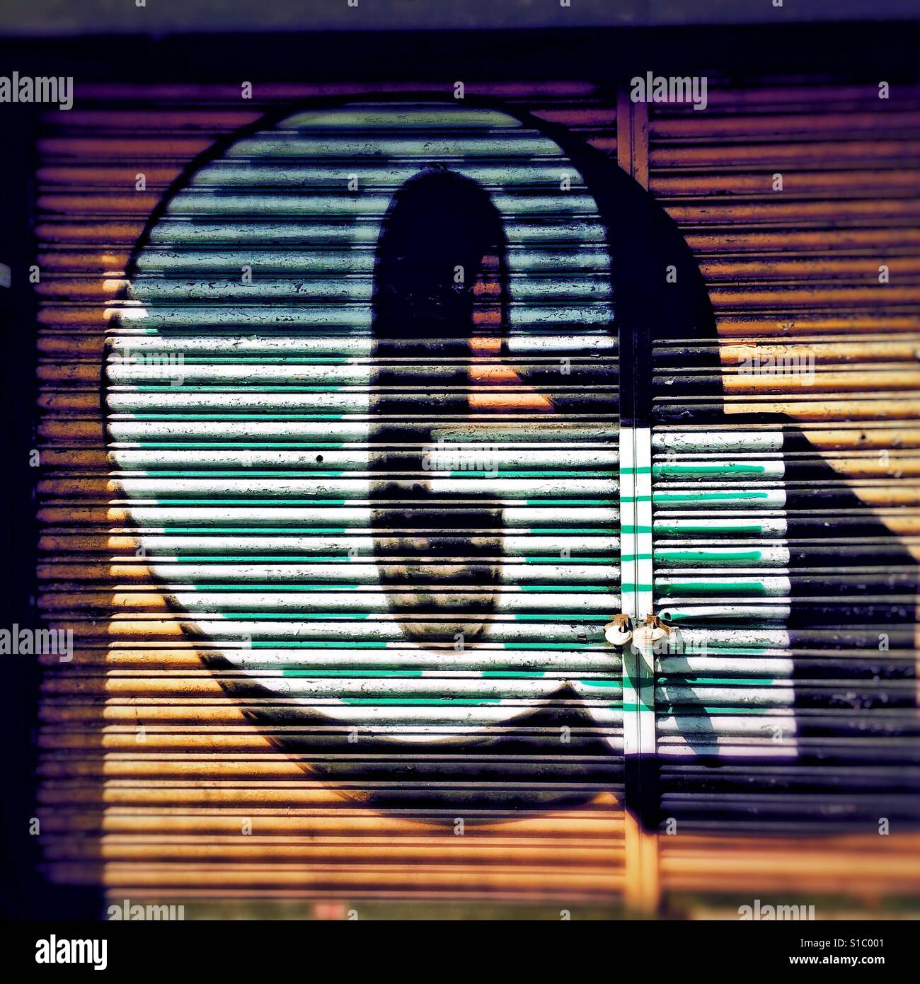 Detail from graffiti art by street artist Ben Eine, showing a colourful, stylised letter G painted onto shutters. - Stock Image