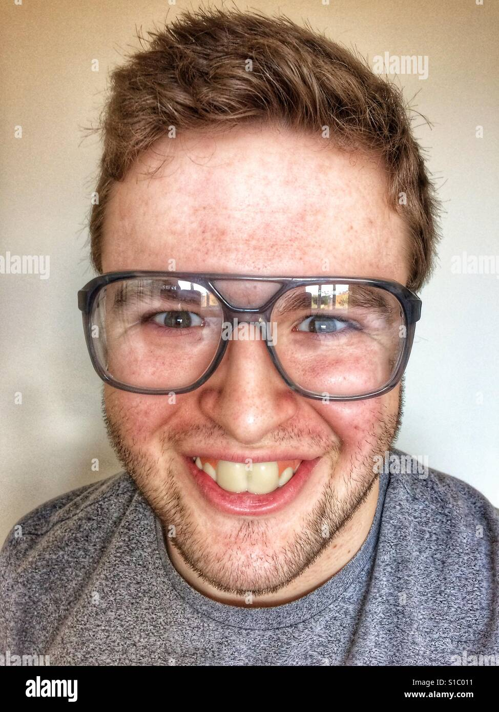 Laughing nerd with buck teeth and big glasses looking straight at the camera. - Stock Image