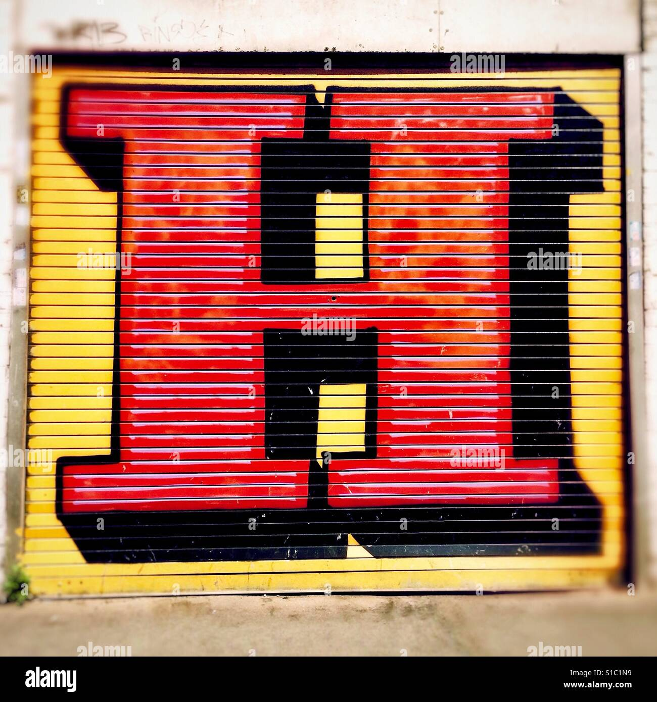 Detail from graffiti art by street artist Ben Eine, showing a colourful, stylised letter H painted onto shutters. - Stock Image