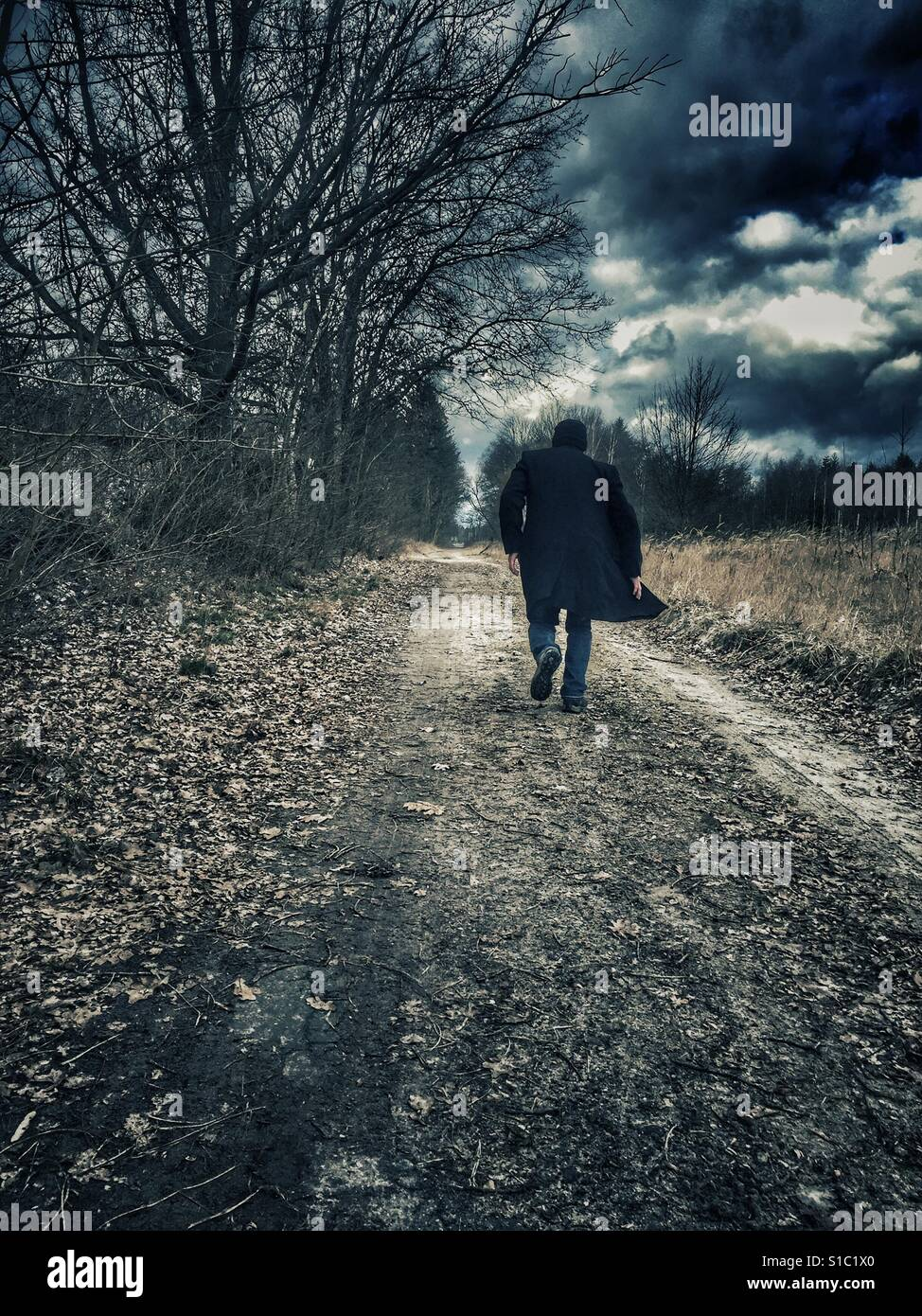 Man wearing a coat running away in the countryside - Stock Image