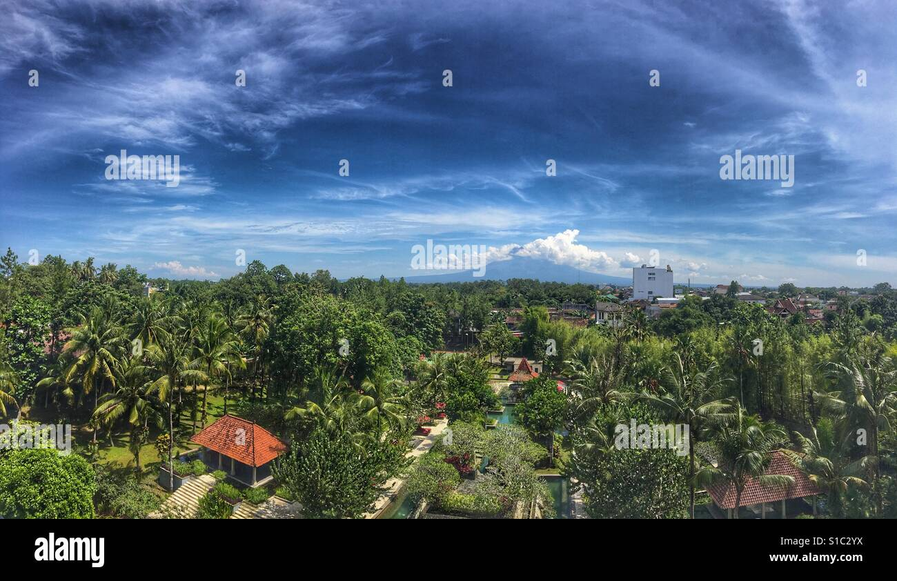 View of cloud-covered Mount Merapi from a rooftop in central Yogyakarta- Java, Indonesia - Stock Image