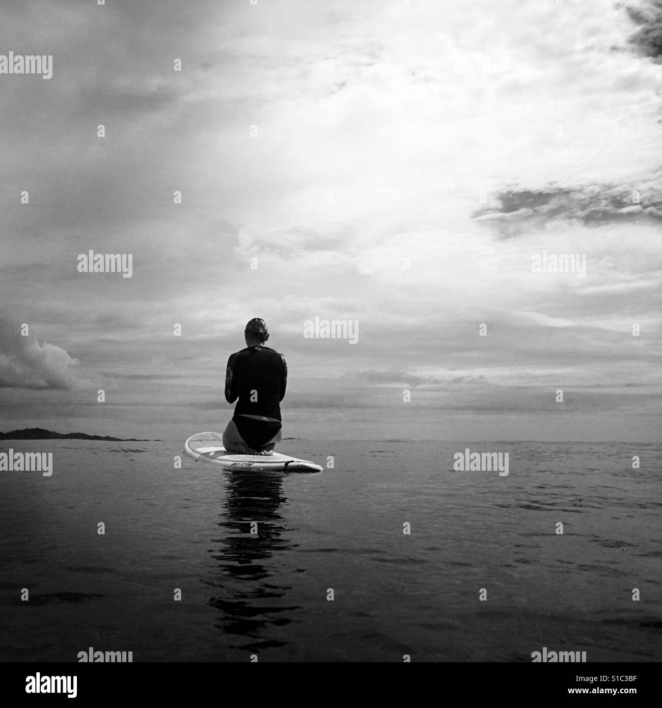 A black and white photo of a young women on a paddle board in the ocean. Tavarua, Fiji. - Stock Image