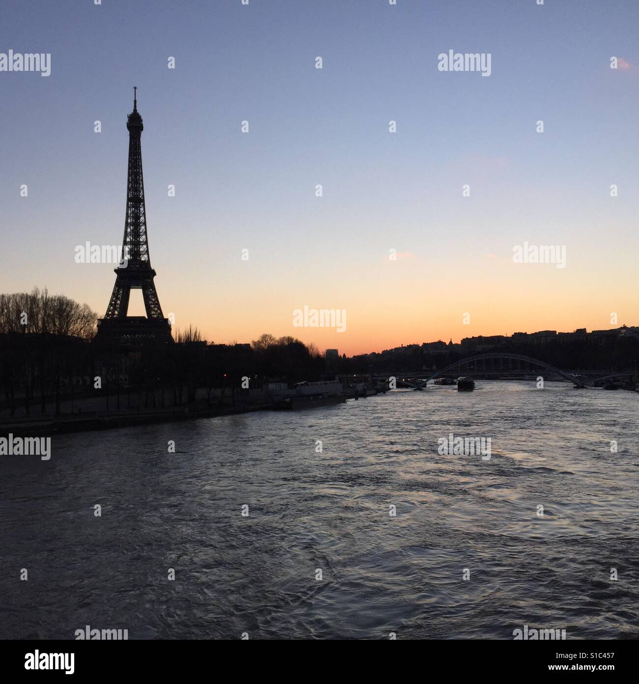 Eiffel Tower in Paris on a winter sunset from a bridge crossing river Seine - Stock Image