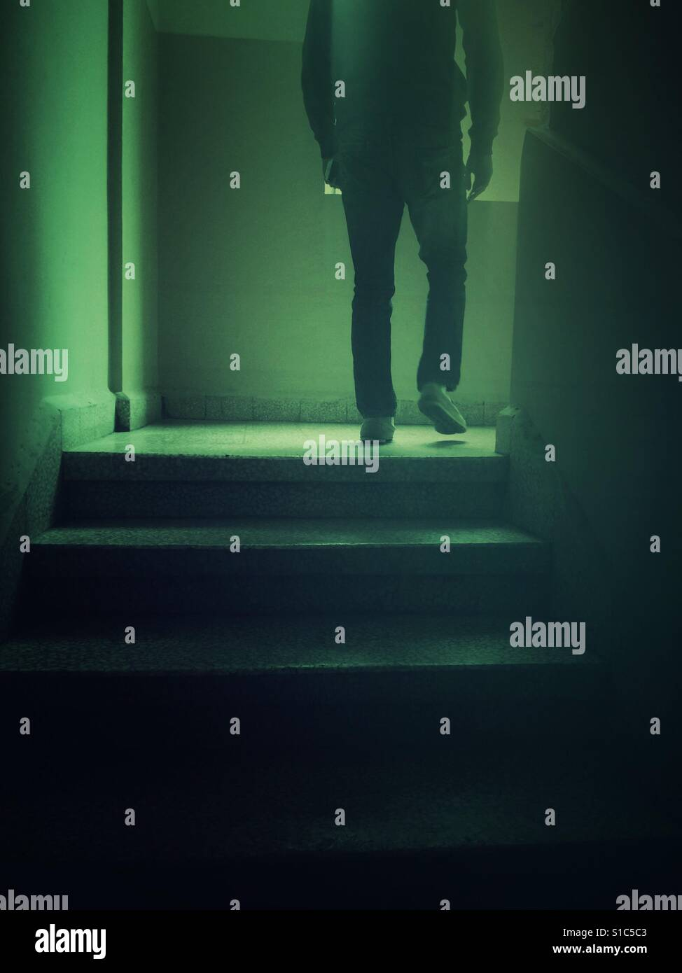 Rear view of a sinister male figure walking up the stairs - Stock Image