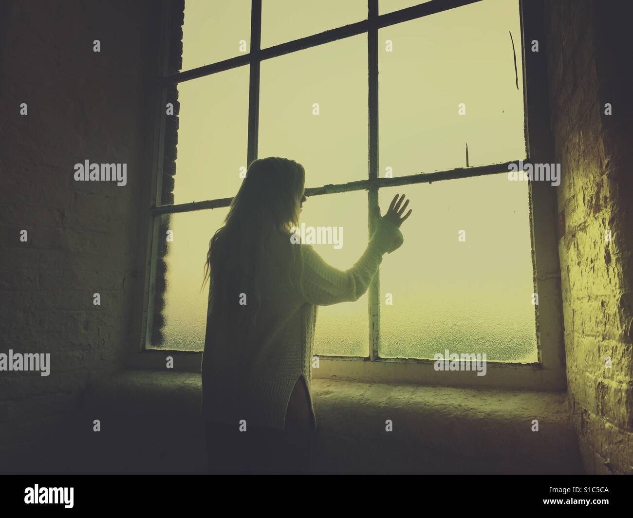 Rear view silhouette of a young woman looking out of the window hand touching the glass - Stock Image