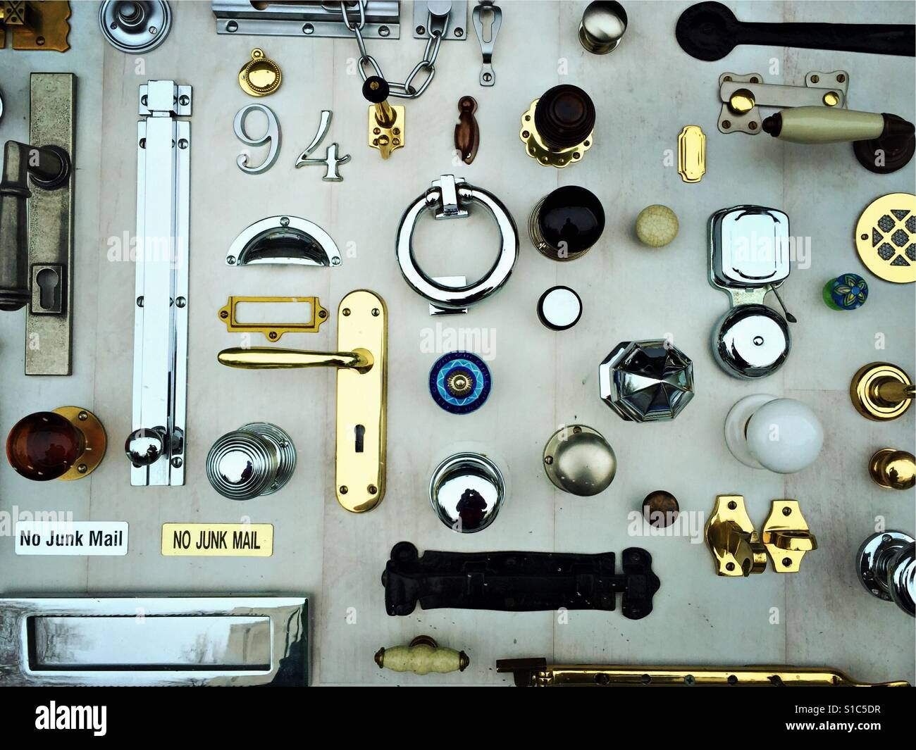 A selection of door furniture including handles and knockers are seen on display in a hardware shop window in Dublin, - Stock Image