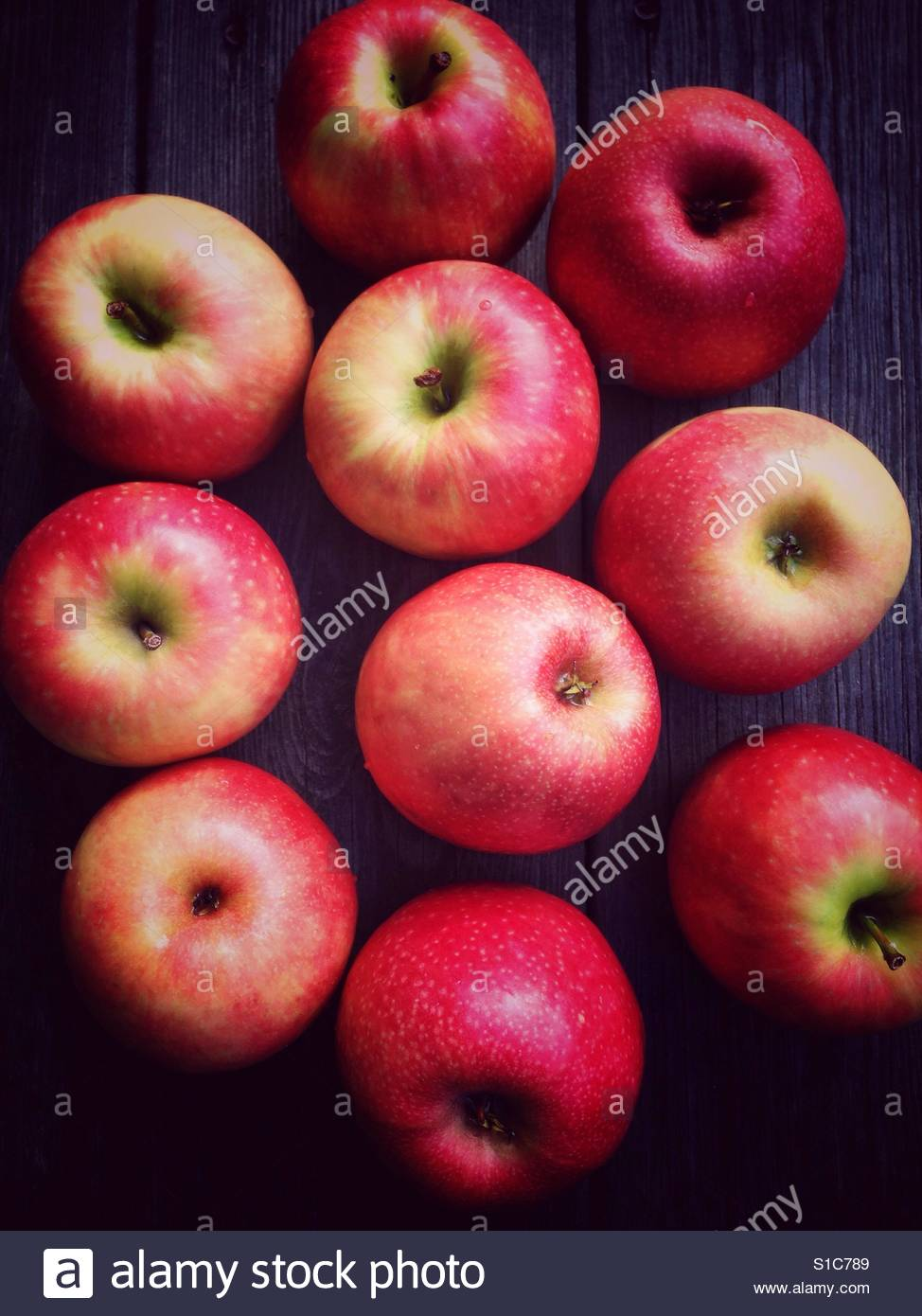 Pink Lady apples on a wooden surface - Stock Image