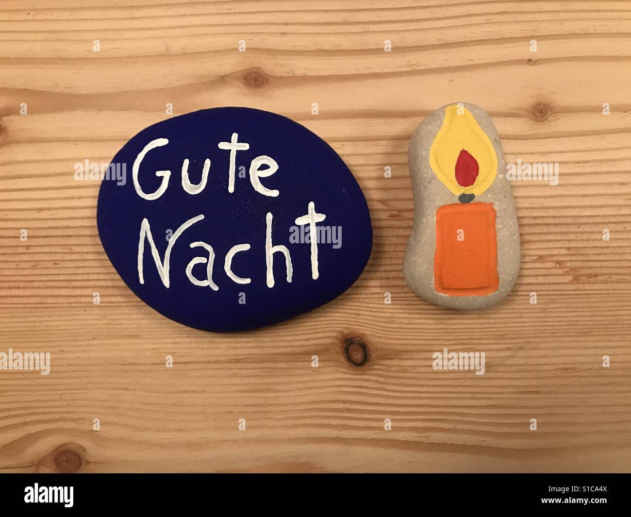 Gute Nacht, german good night with colored stones over wooden board - Stock Image