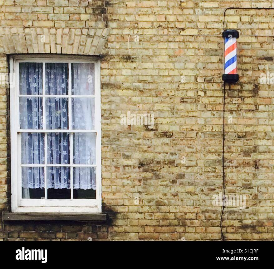 Old fashioned barbershop with modern electric pole. - Stock Image