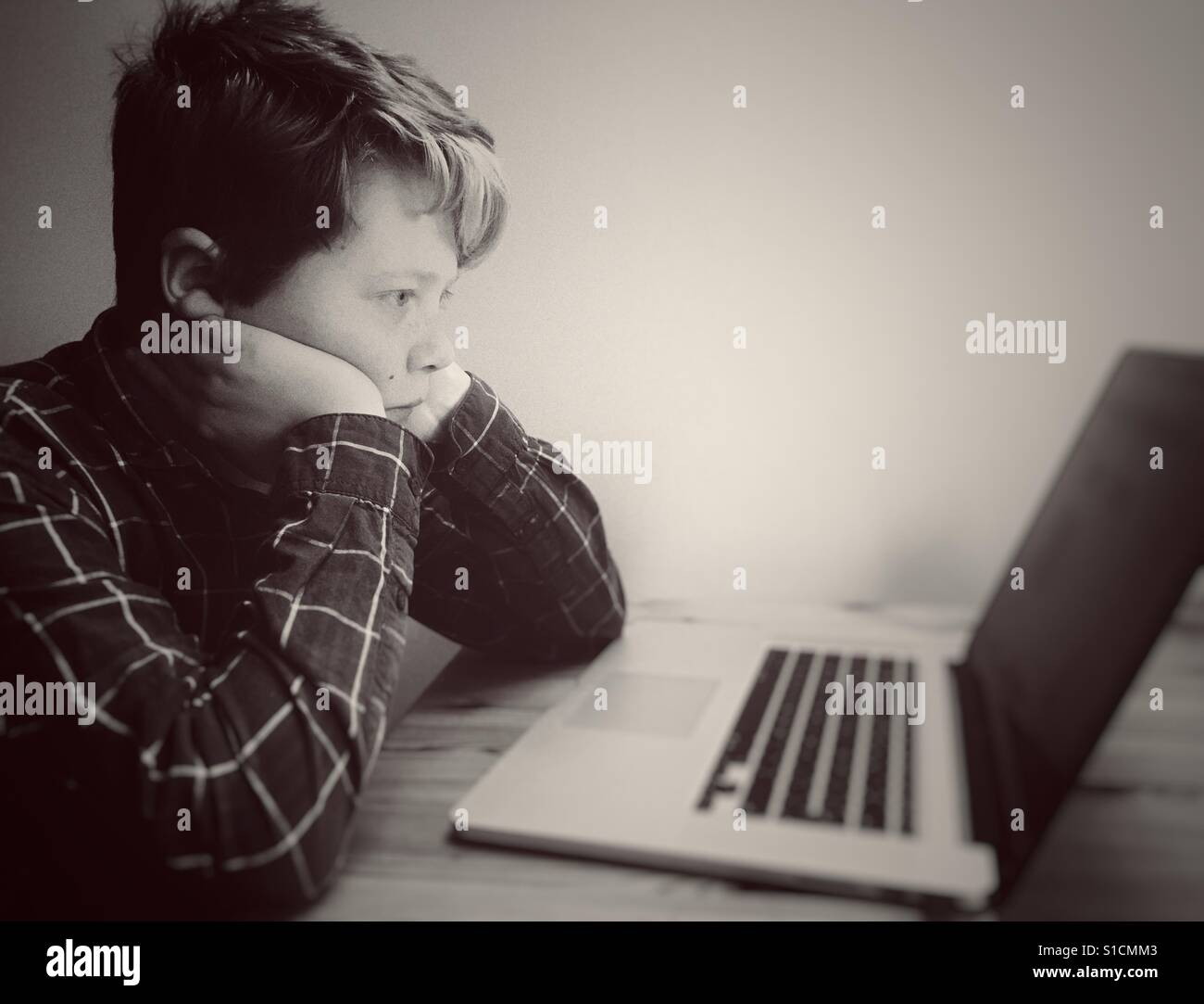 11-year old boy using laptop computer - Stock Image
