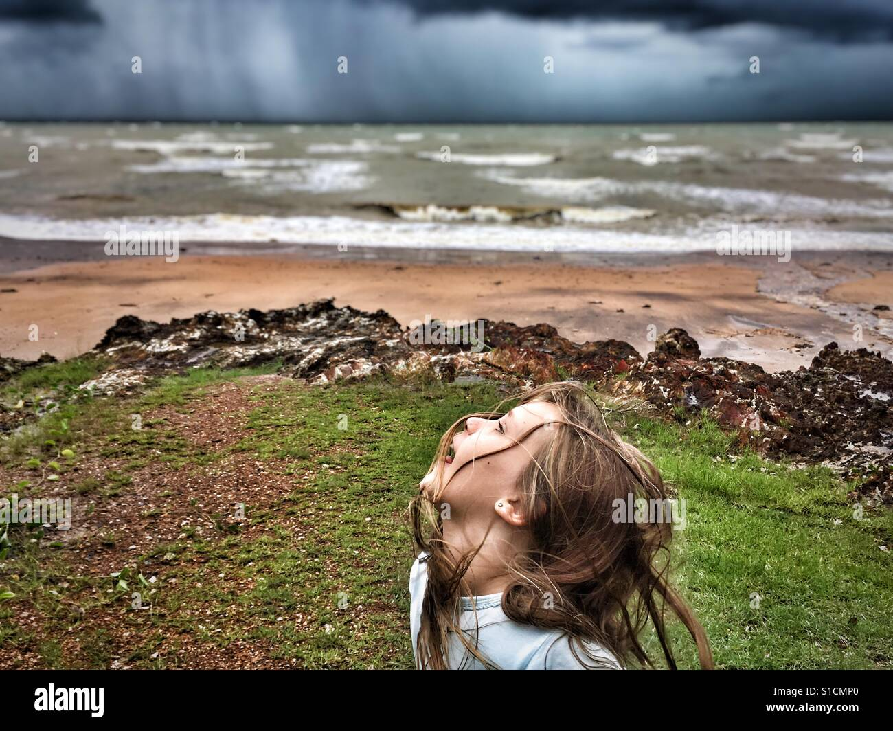 Child playing in front of the incoming storm. - Stock Image