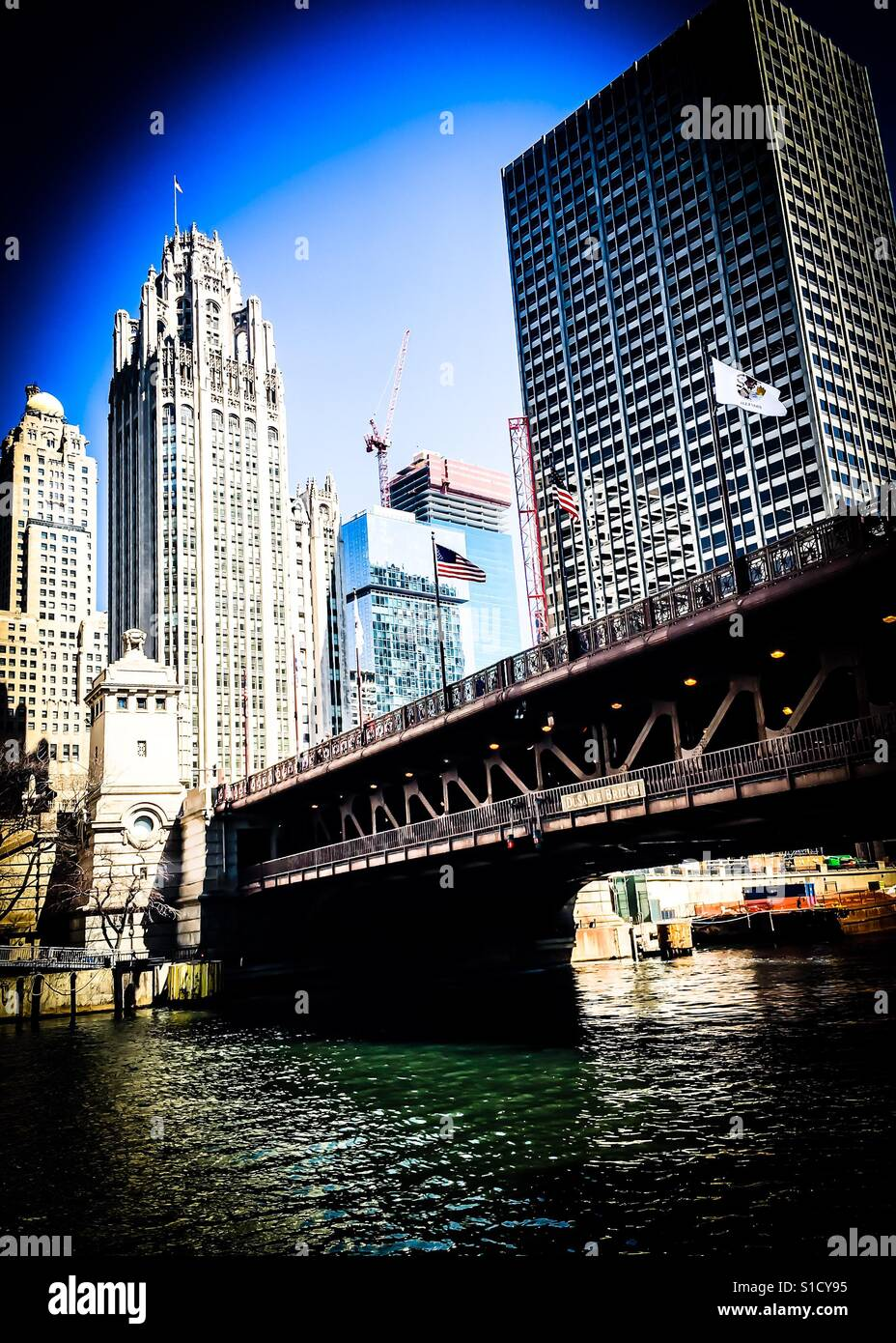 American and Chicago flags flying in the windy city over the Michigan Avenue bridge on a crisp spring afternoon - Stock Image