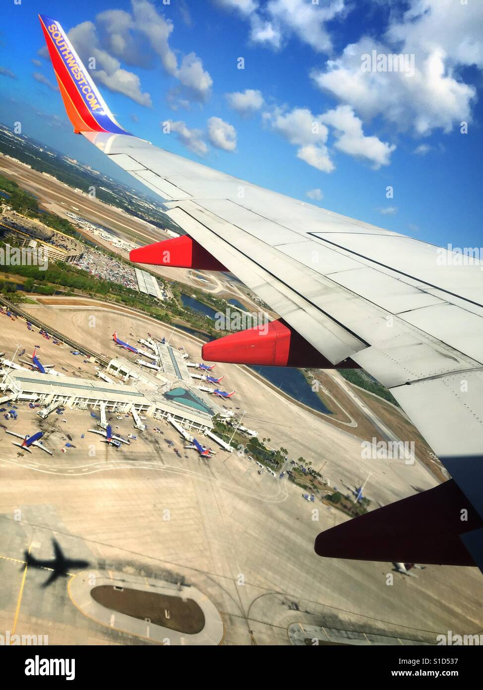 A photo of an airport and  a plane's shadow as it takes off on a bright, sunny day. - Stock Image