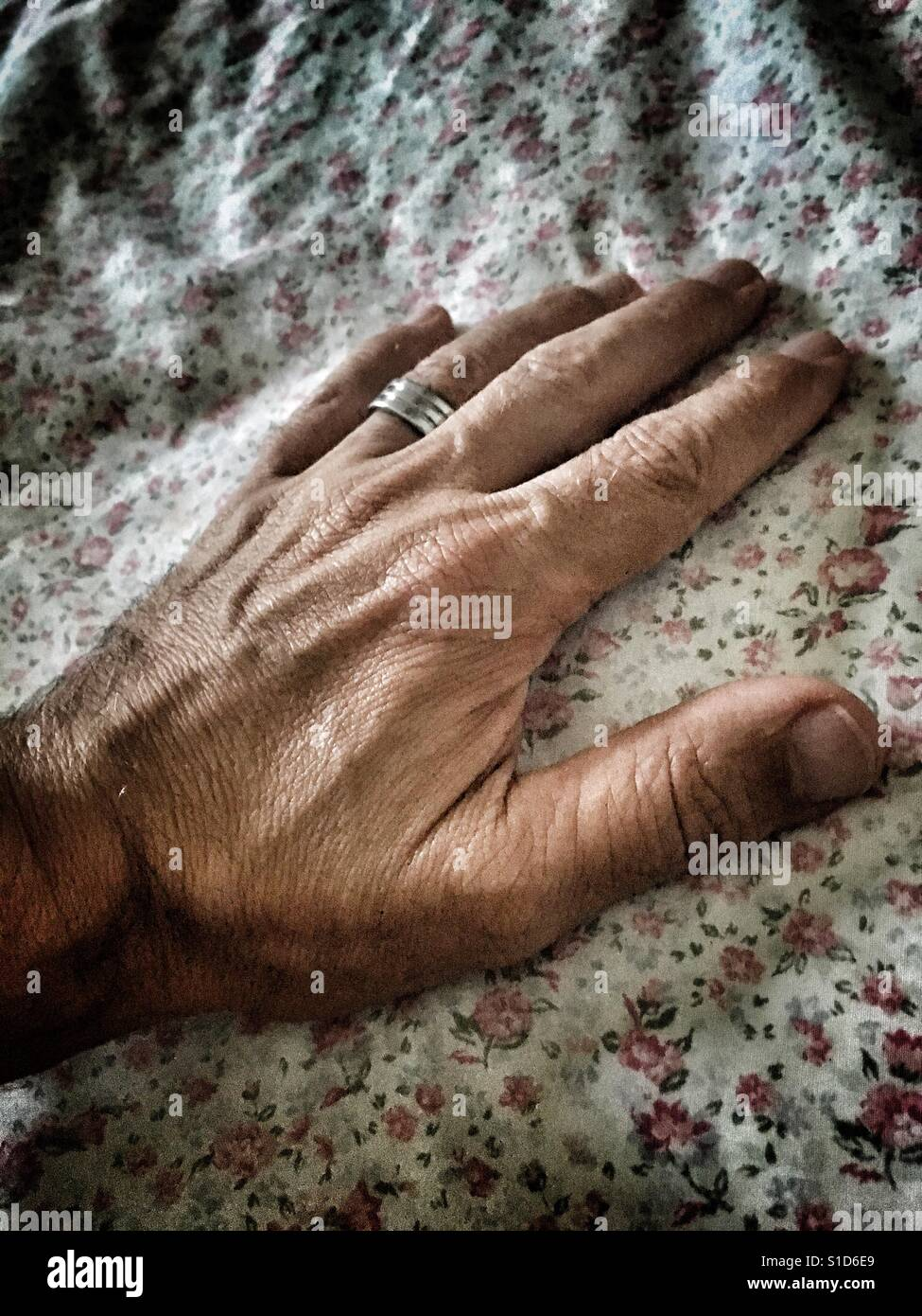 Man's hand on a vintage fabric. - Stock Image