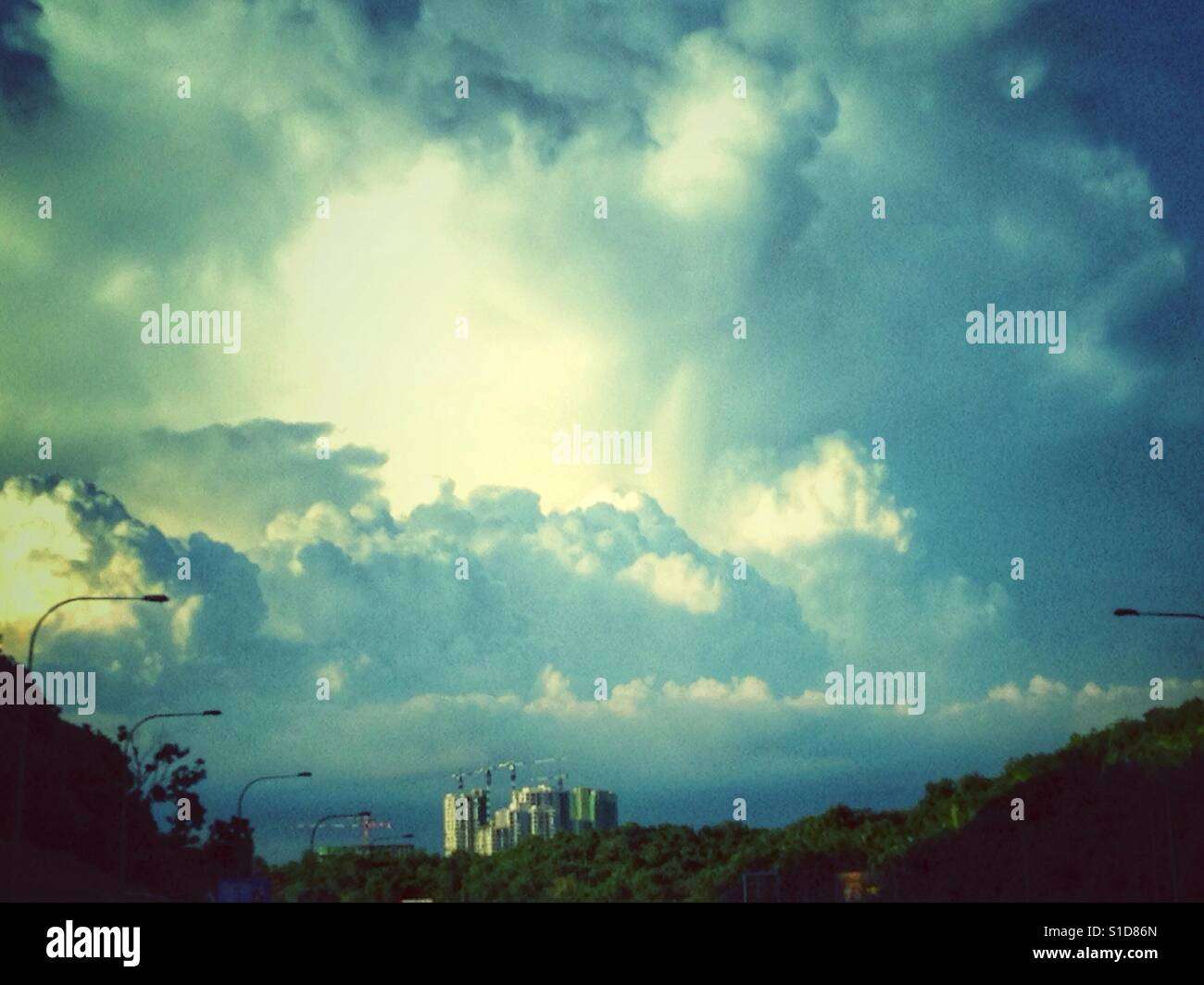 Large Cumulonimbus clouds over building on hill top - Stock Image