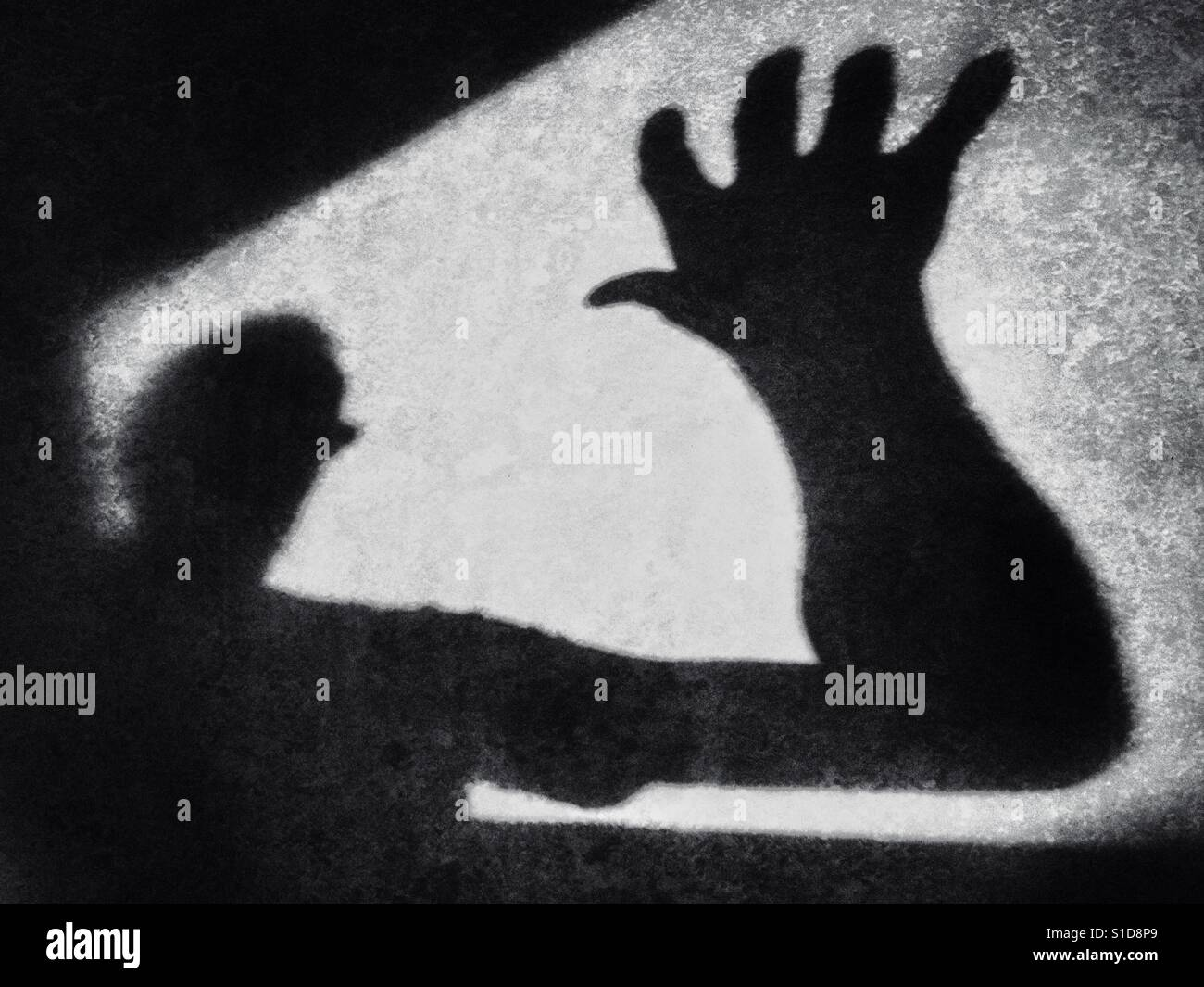 Shadowy figure making a grab. Conceptual image of fear of the unknown - Stock Image