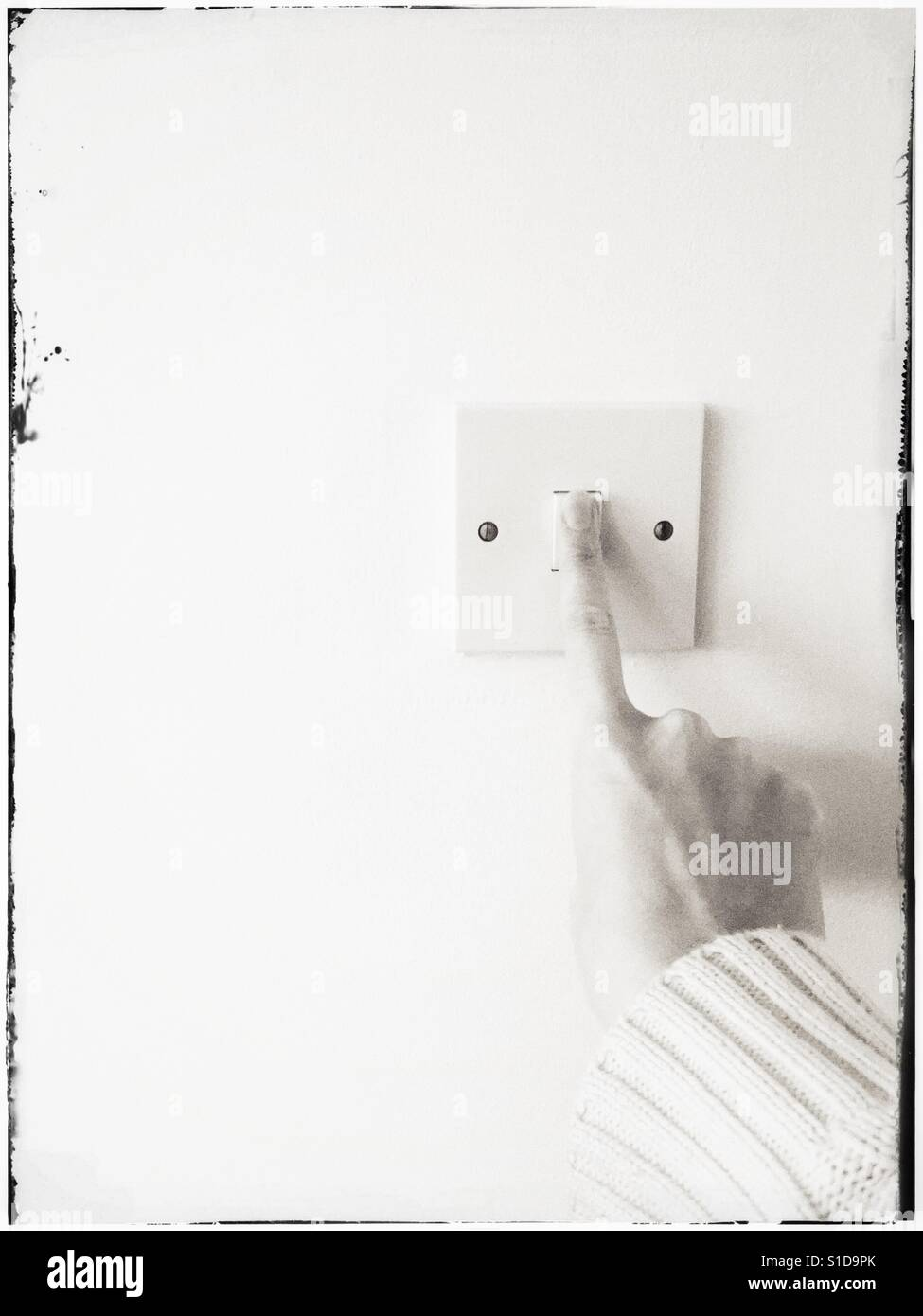 Index finger on right hand turning on or off an electric light switch. Muted tones with grain and retro filter applied. - Stock Image