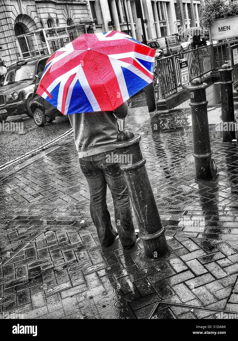 Black And White Selective Colour Photo Of A Man Standing In Rain Shower While Holding Colourful Union Flag Umbrella Near Carnaby Street London