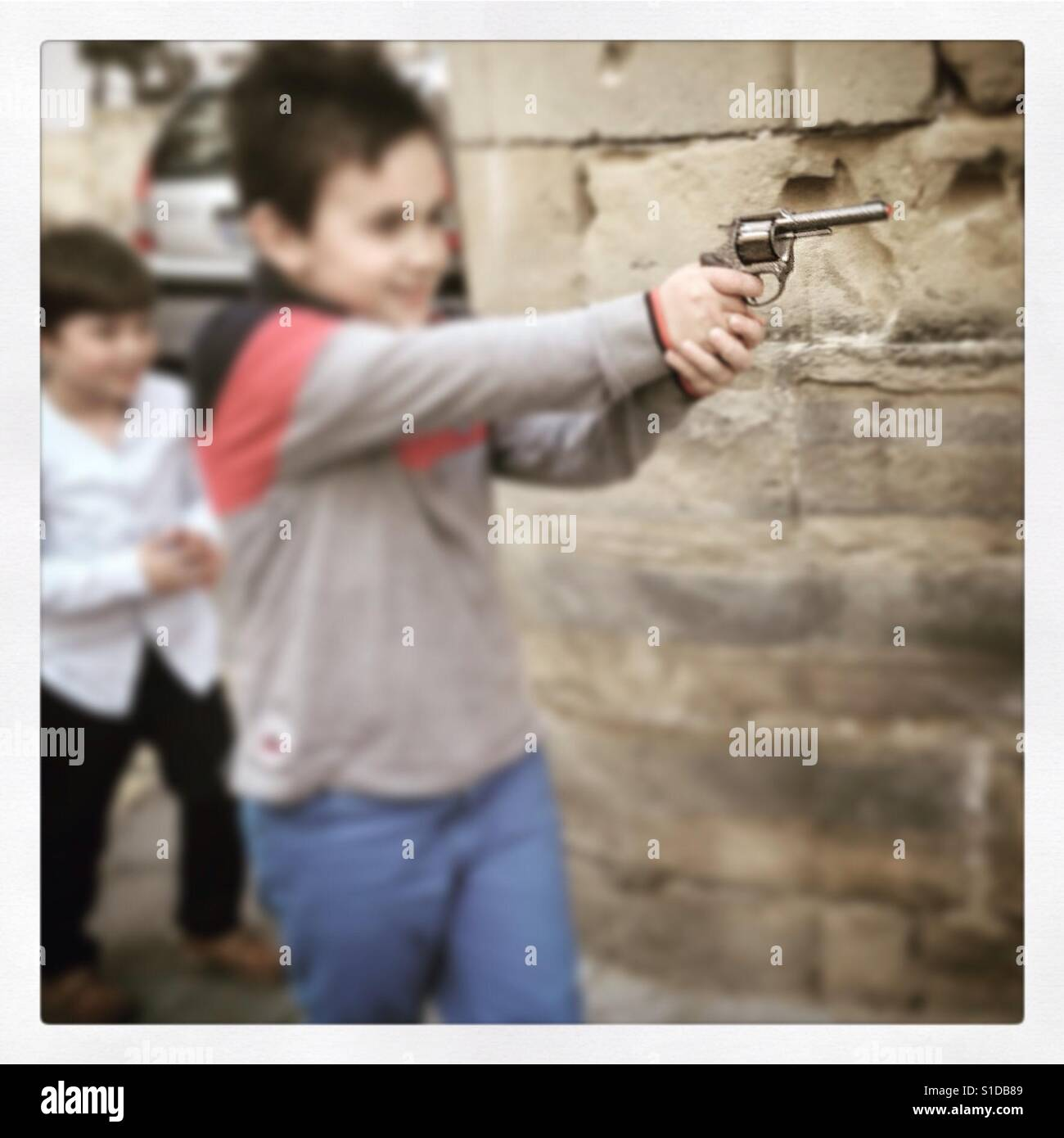 Boy pointd toy gun as he pretends to shoot his friends in Andalusian town Baeza in southern Spain. - Stock Image