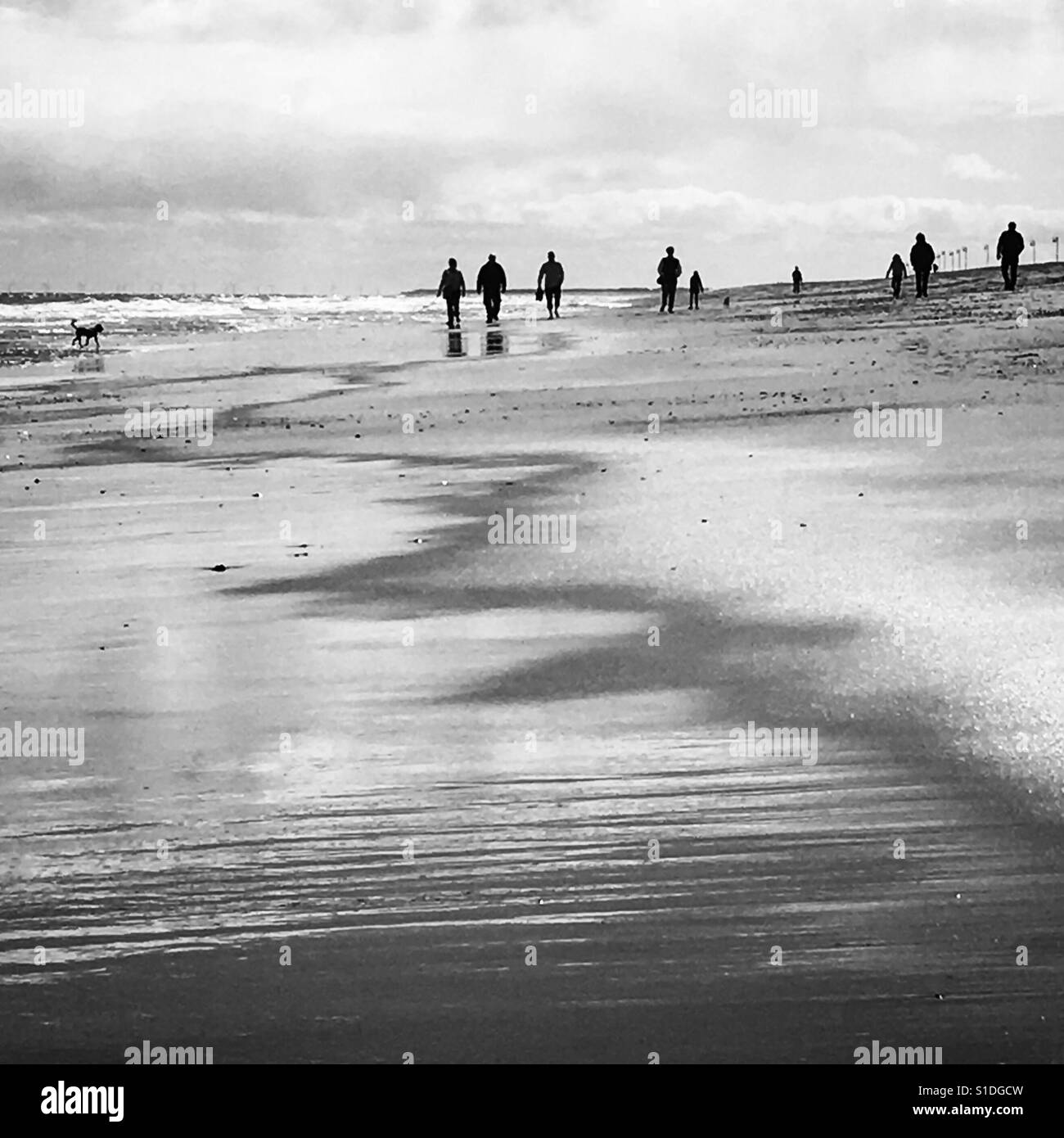 People walking along the beach. - Stock Image