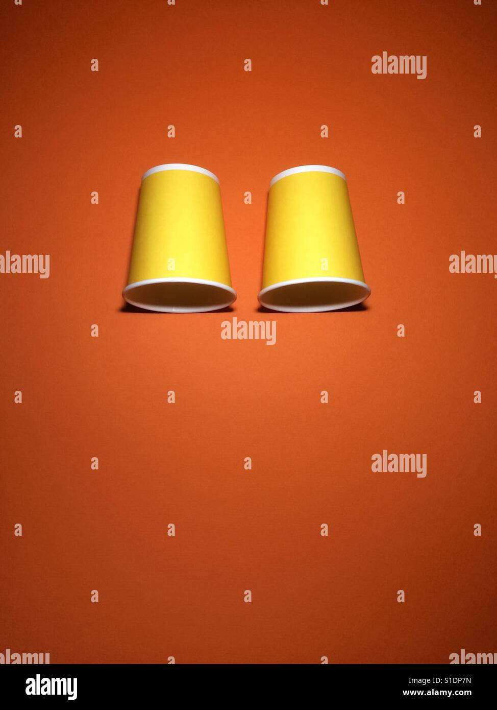 Two yellow disposable cups on orange textured paper background with copy space. - Stock Image