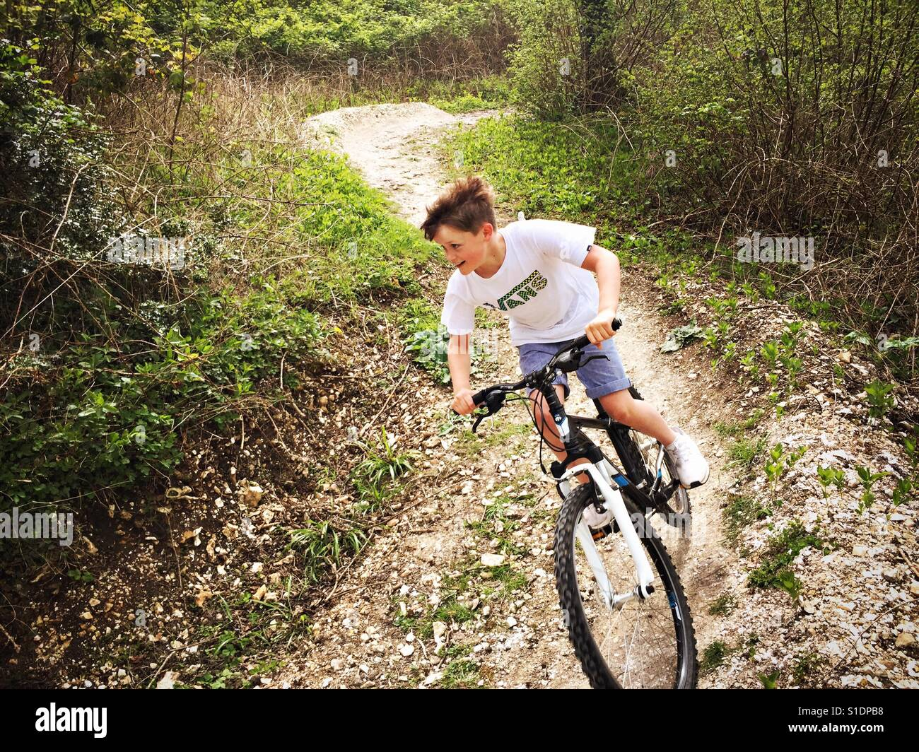 An 11-year-old boy rides his mountain bike down a trail in woodland