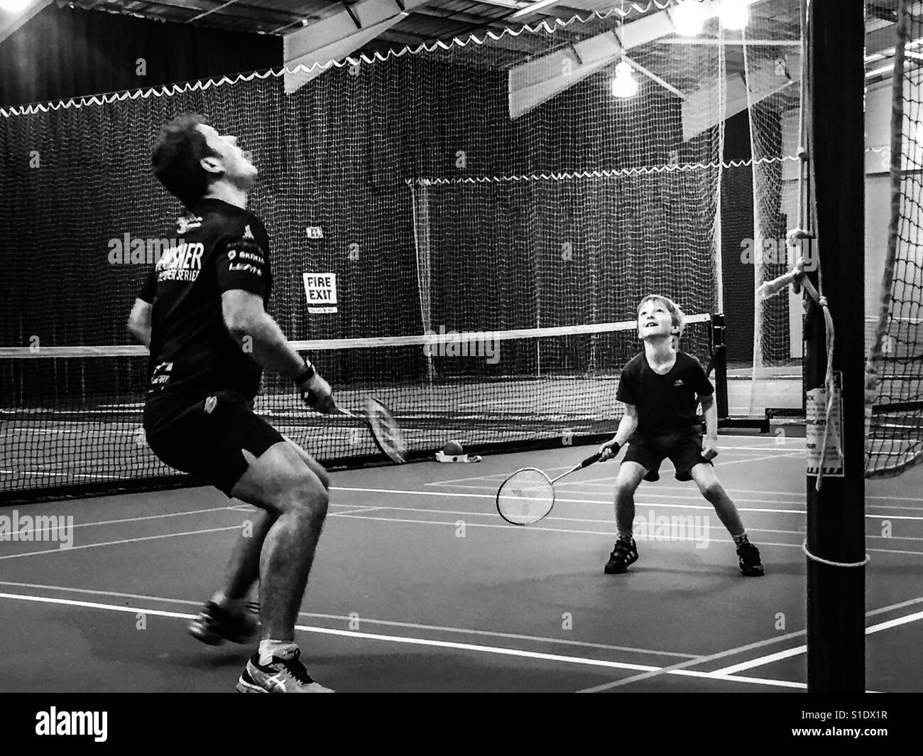 Father and son play badminton doubles. - Stock Image