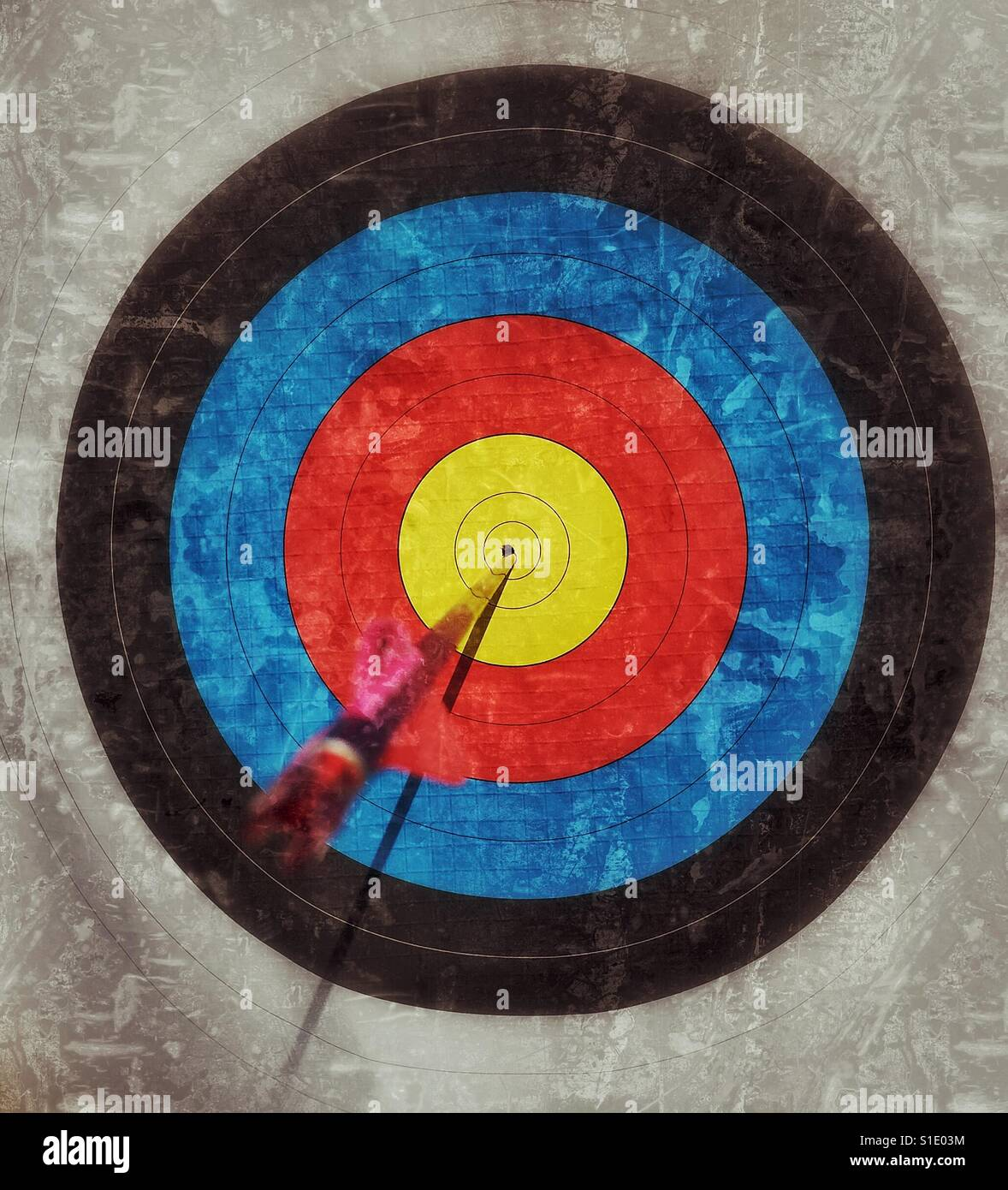 BULLSEYE! The perfect archery shot. A grunge effect image of an arrow in the dead centre of an archery target. Photo - Stock Image
