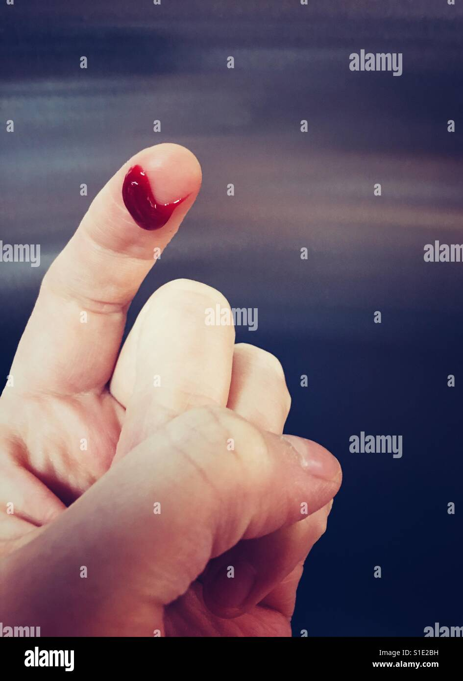 Human finger with a blood drop - Stock Image