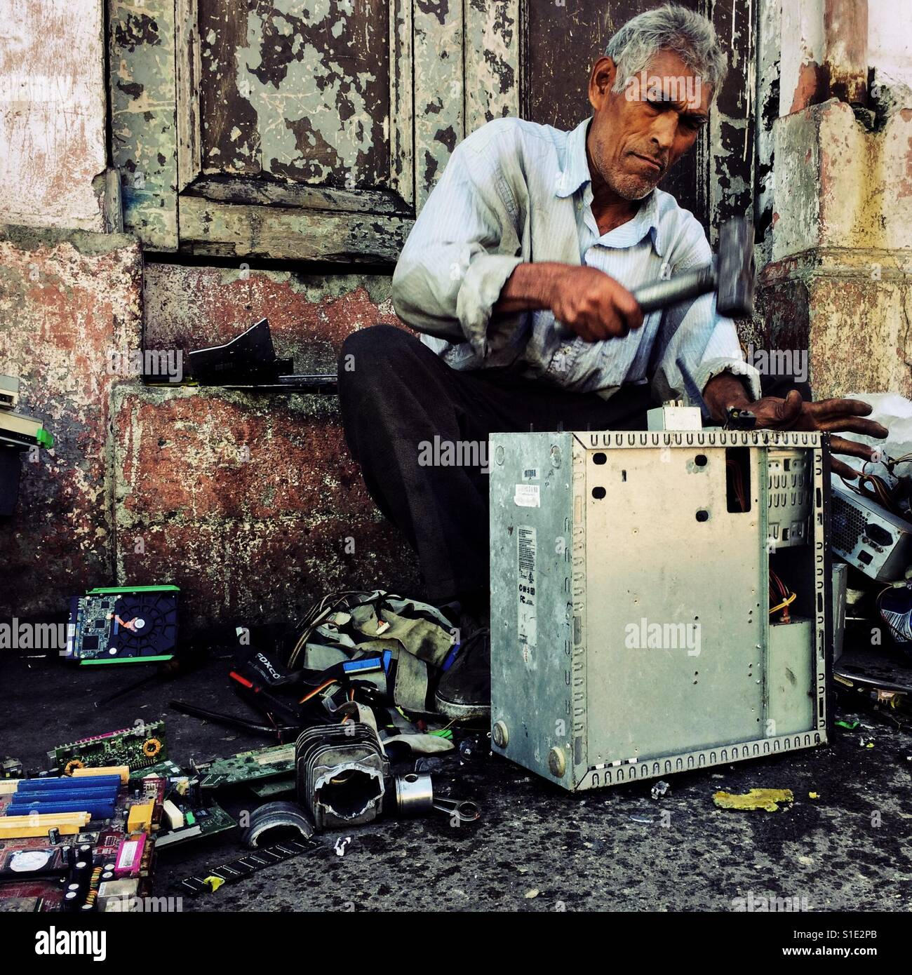 A Salvadoran recycler dismantles an old desktop computer to obtain valuable components and metals on the street - Stock Image