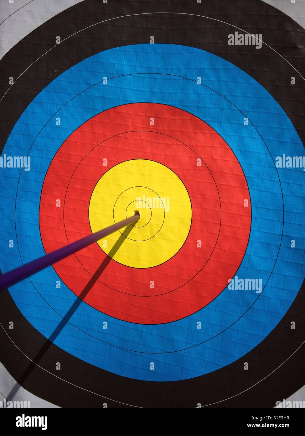 BULLSEYE! A single arrow hits the dead centre of an archery target. A concept image to illustrate perfection. Photo Stock Photo