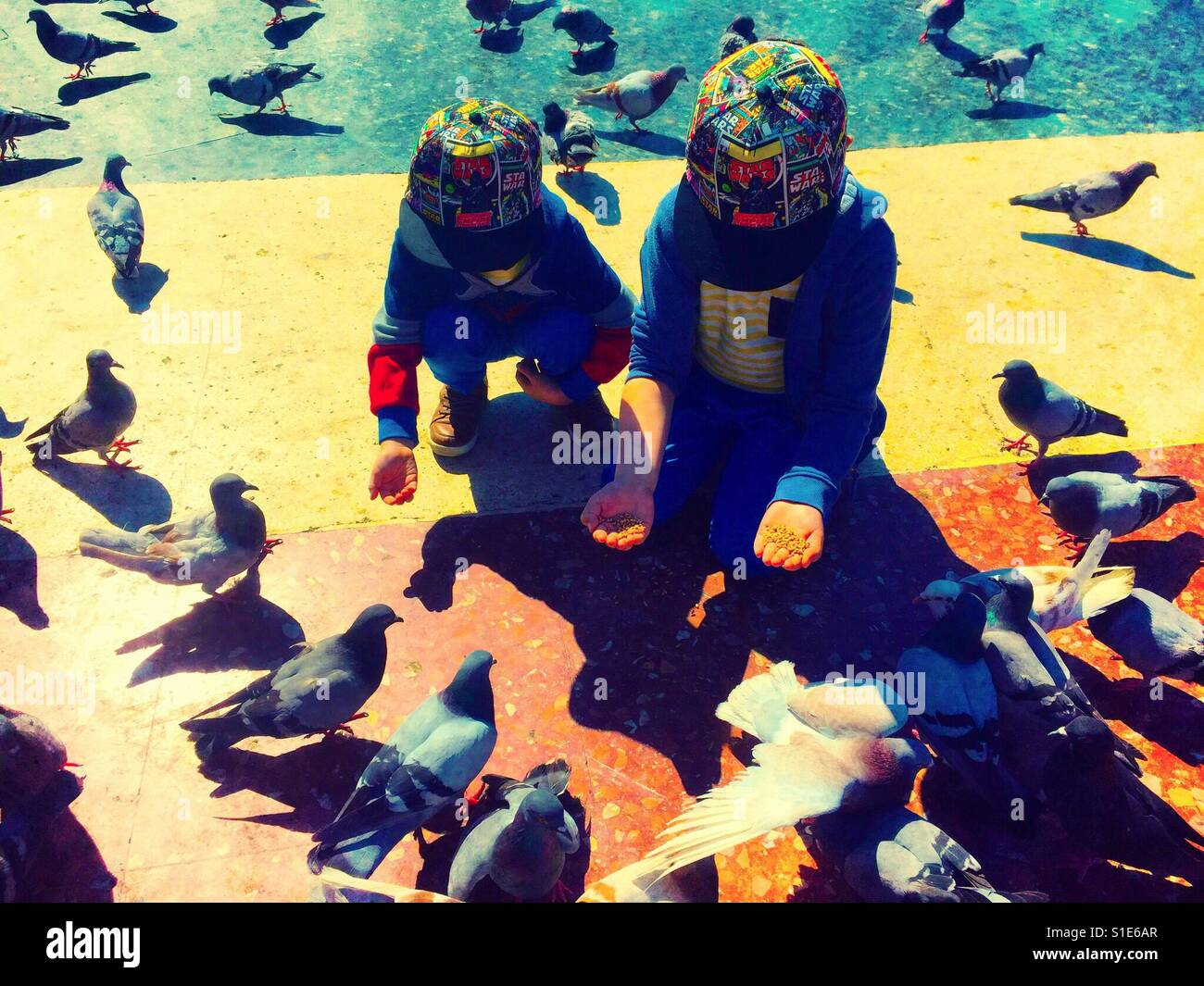 Two young brothers squat and kneel down to feed pigeons. - Stock Image