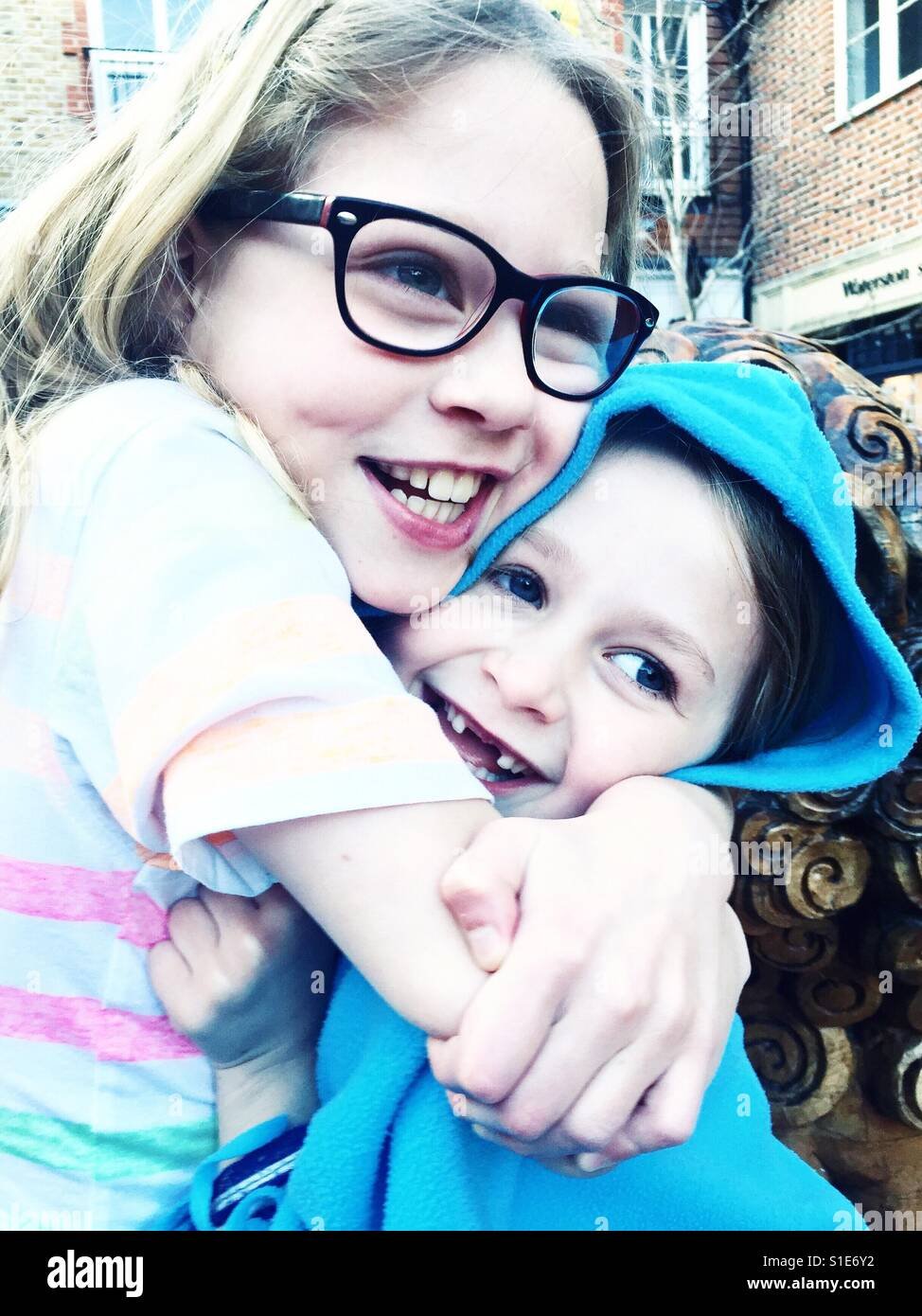 Sisters cuddling - Stock Image