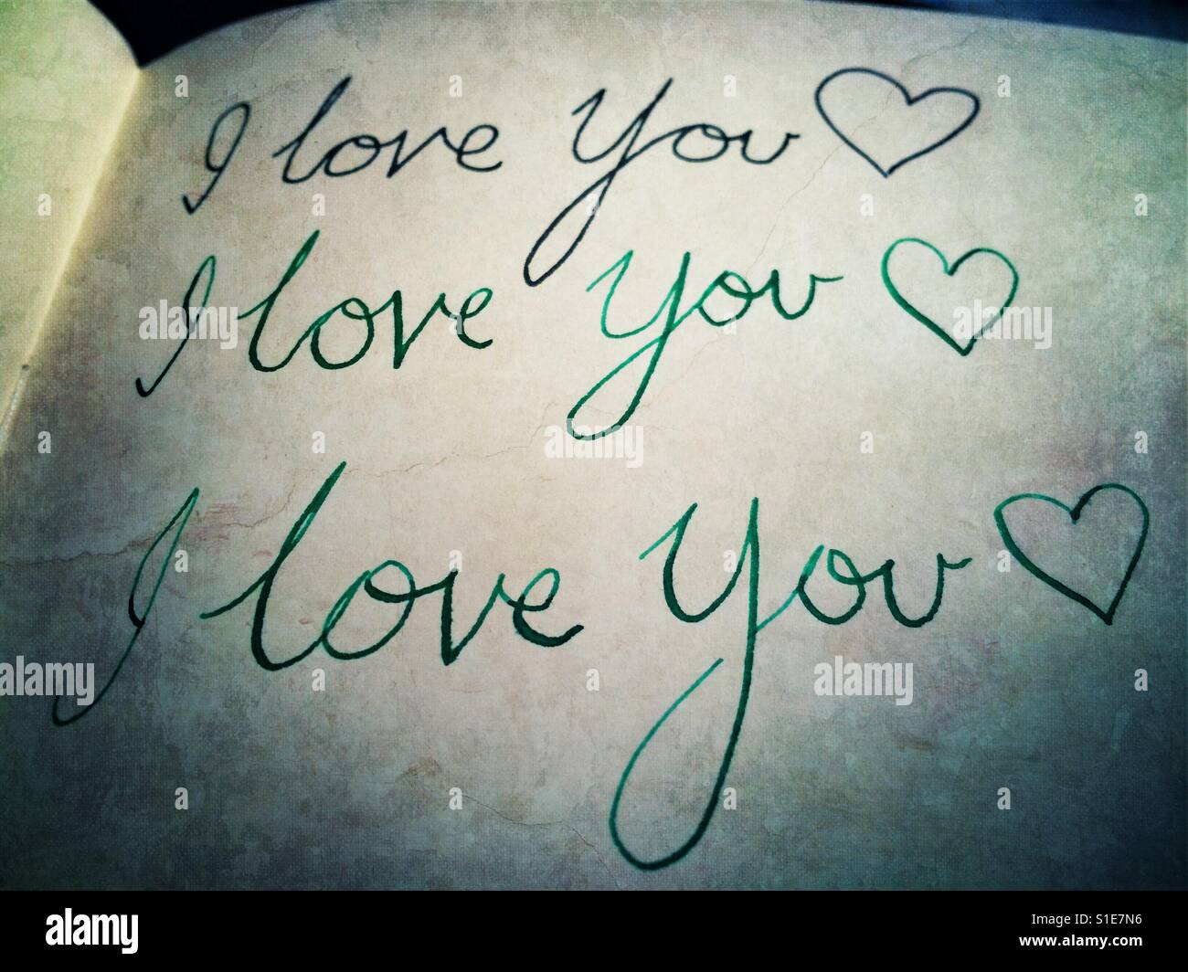 I love you written on a notebook over and over - Stock Image
