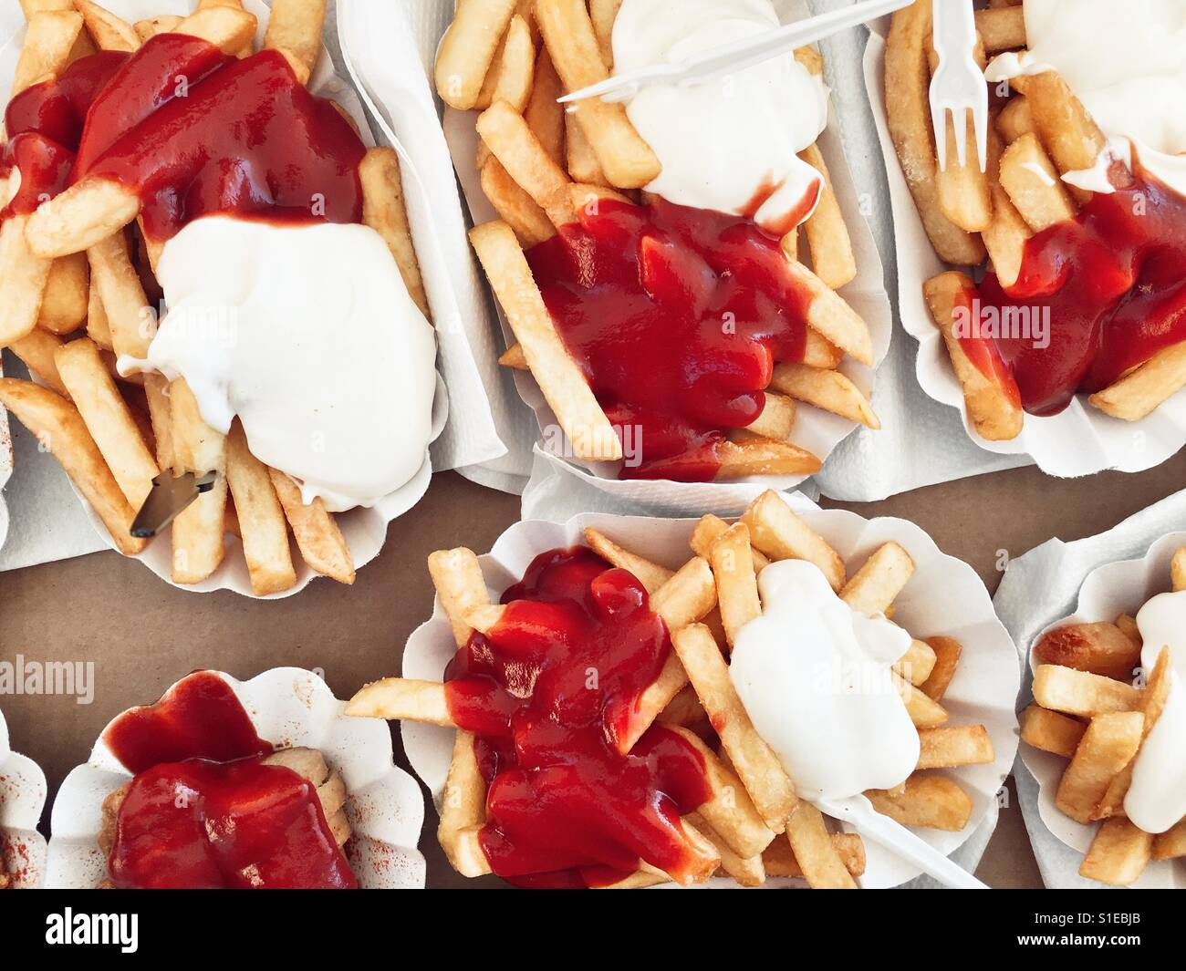 Paper plates of fries with ketchup and mayonnaise and curry sausage & Paper plates of fries with ketchup and mayonnaise and curry sausage ...