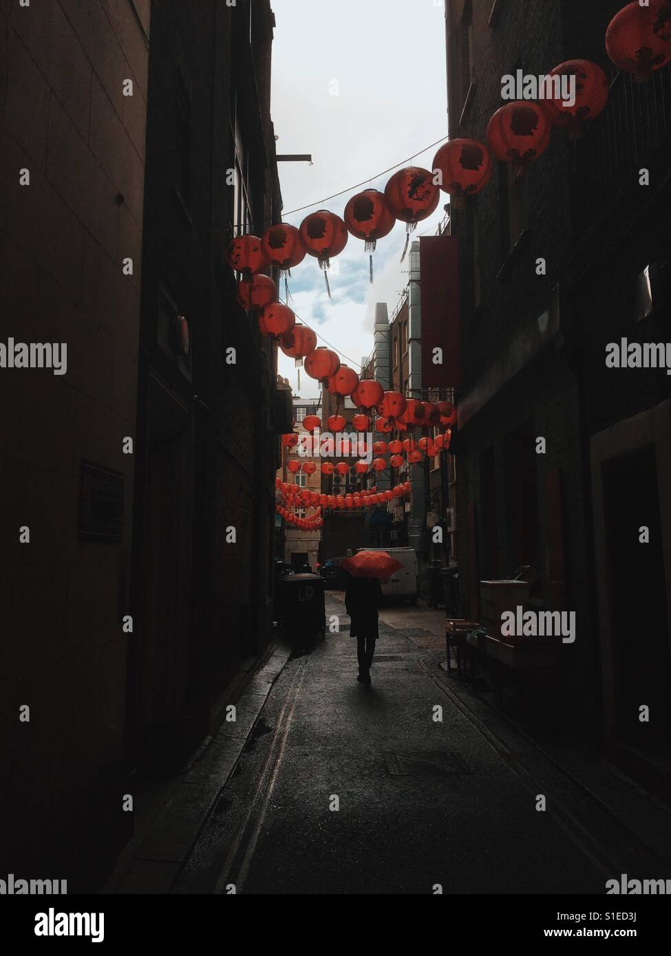 Man with a red umbrella waking in London's China Town Soho May 2017 - Stock Image