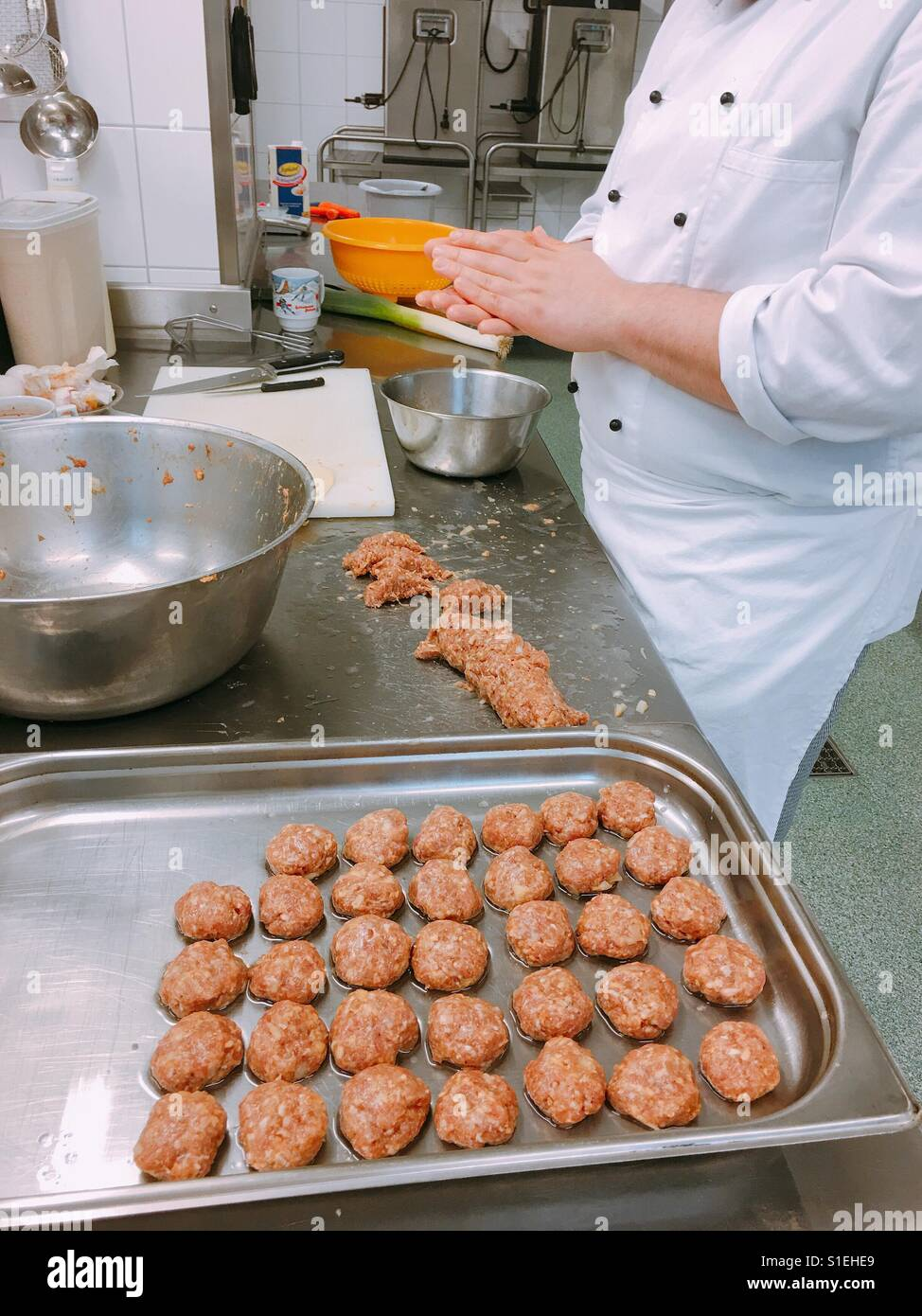 A young trainee cook makes meatballs in the kitchen - Stock Image