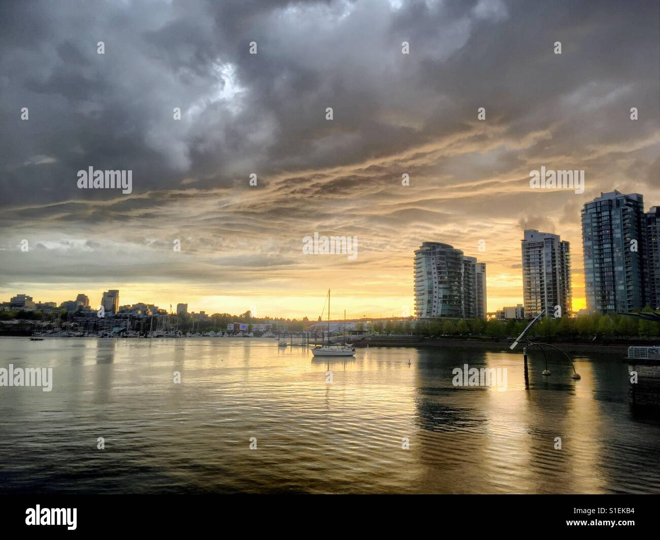 Sunset in Vancouver at False Creek. On the right site there a three high riser. In front the water, clouds are grey - Stock Image