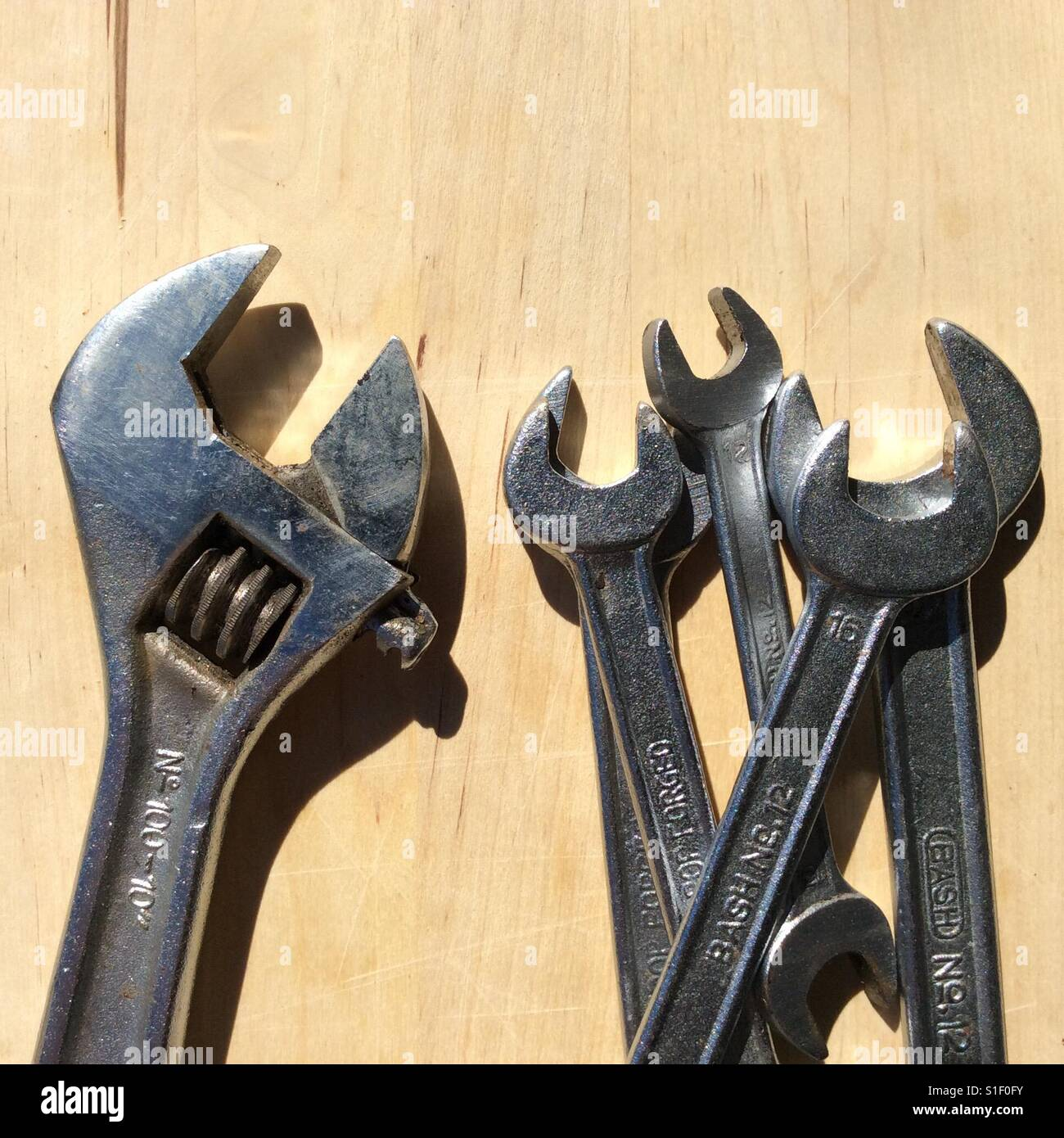 Adjustable wrench versus open end wrenches - Stock Image