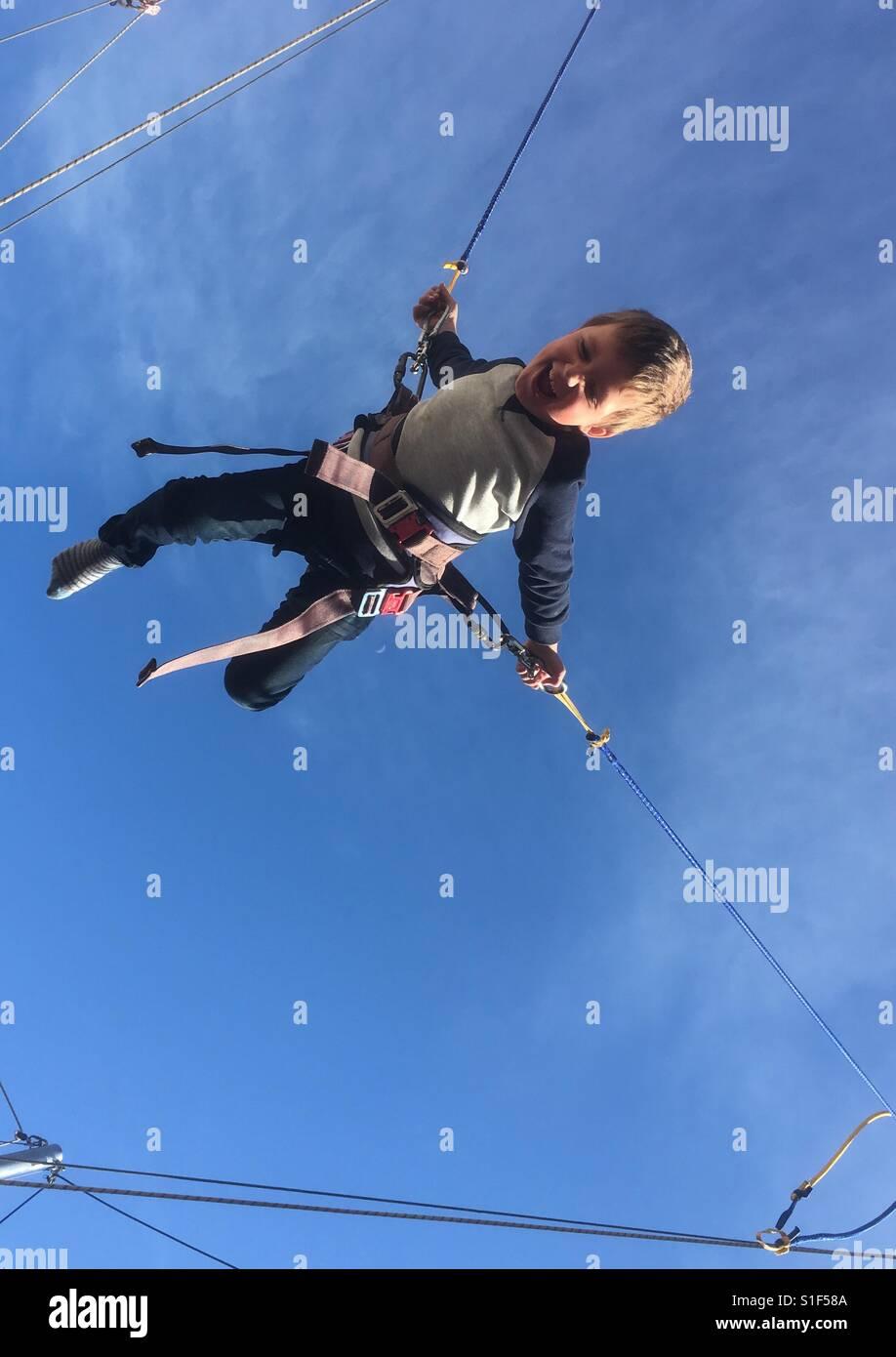 Boy bouncing on elastic rope - Stock Image